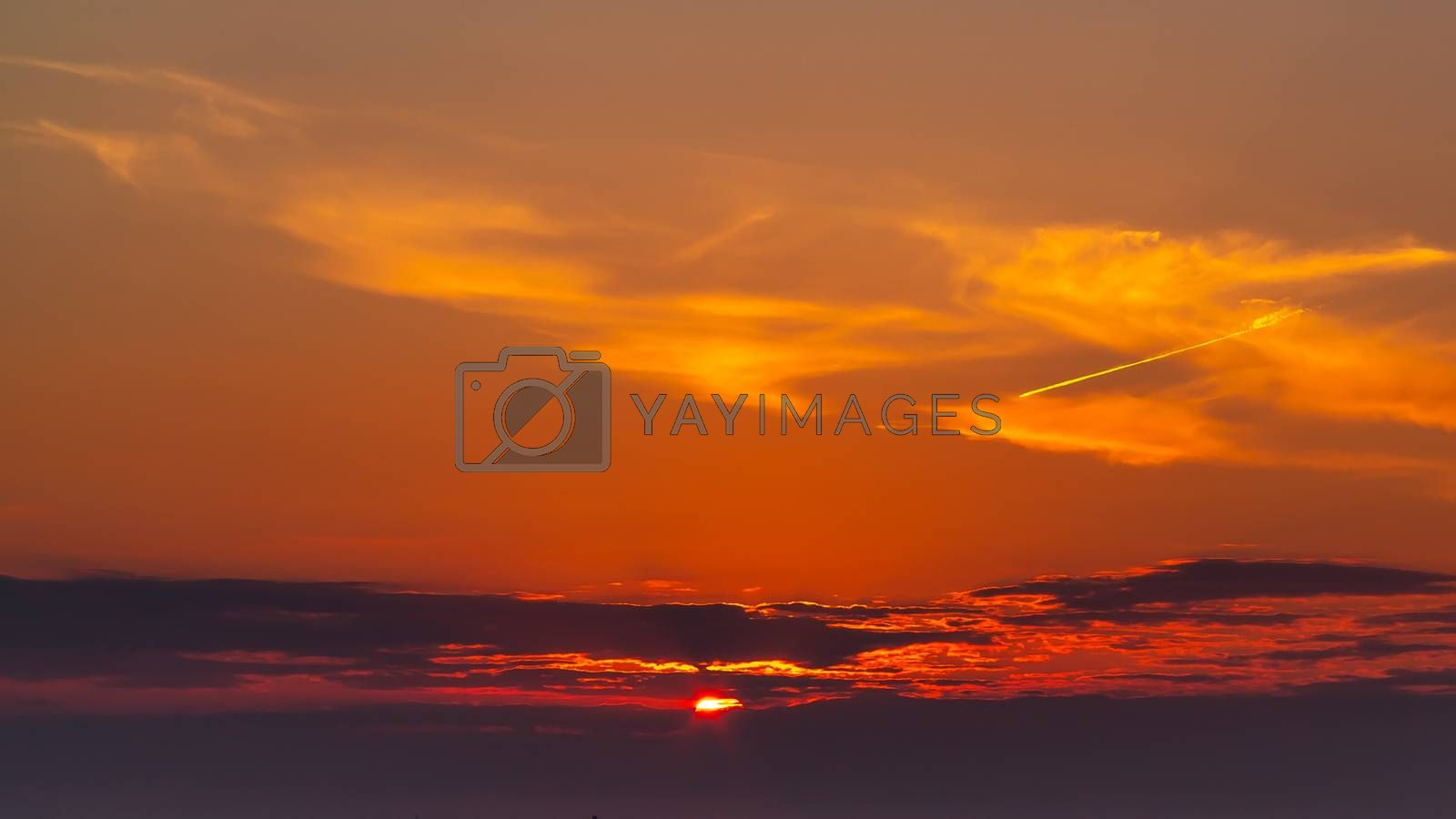 sky during a colorful, bright orange sunset, sun's rays make their way through the clouds by galsand