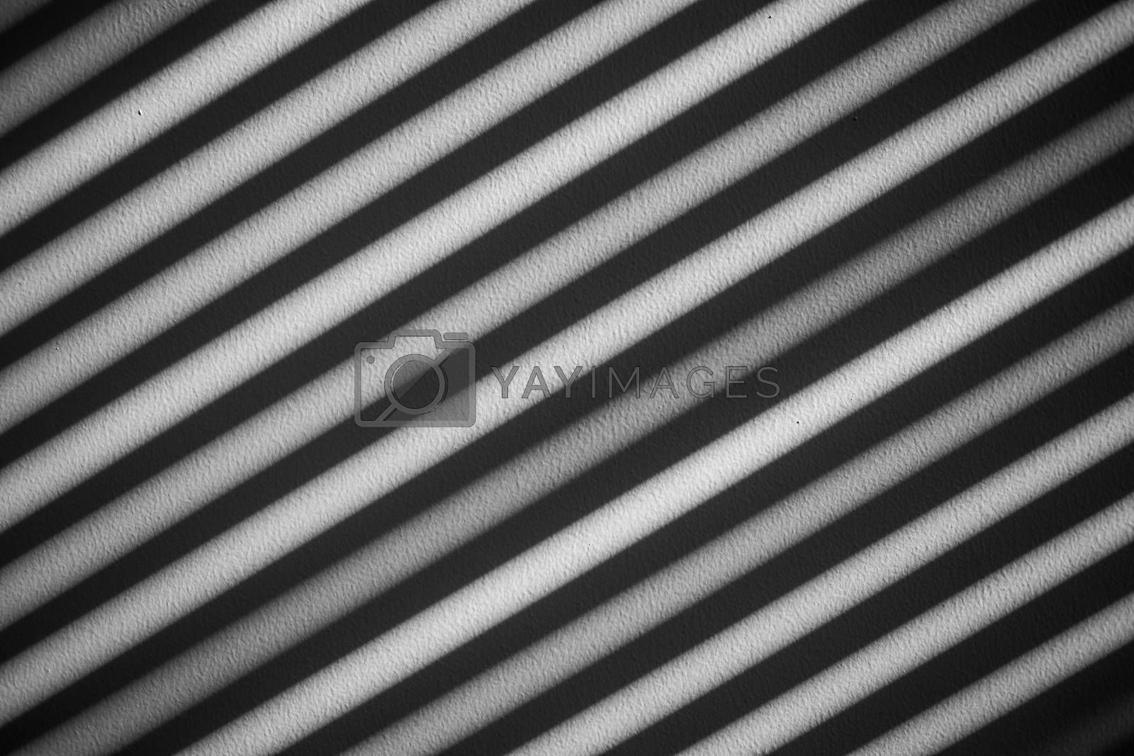 Abstract black and white scene of shining sunlight in diagonal lines on rough wall surface in different shades.