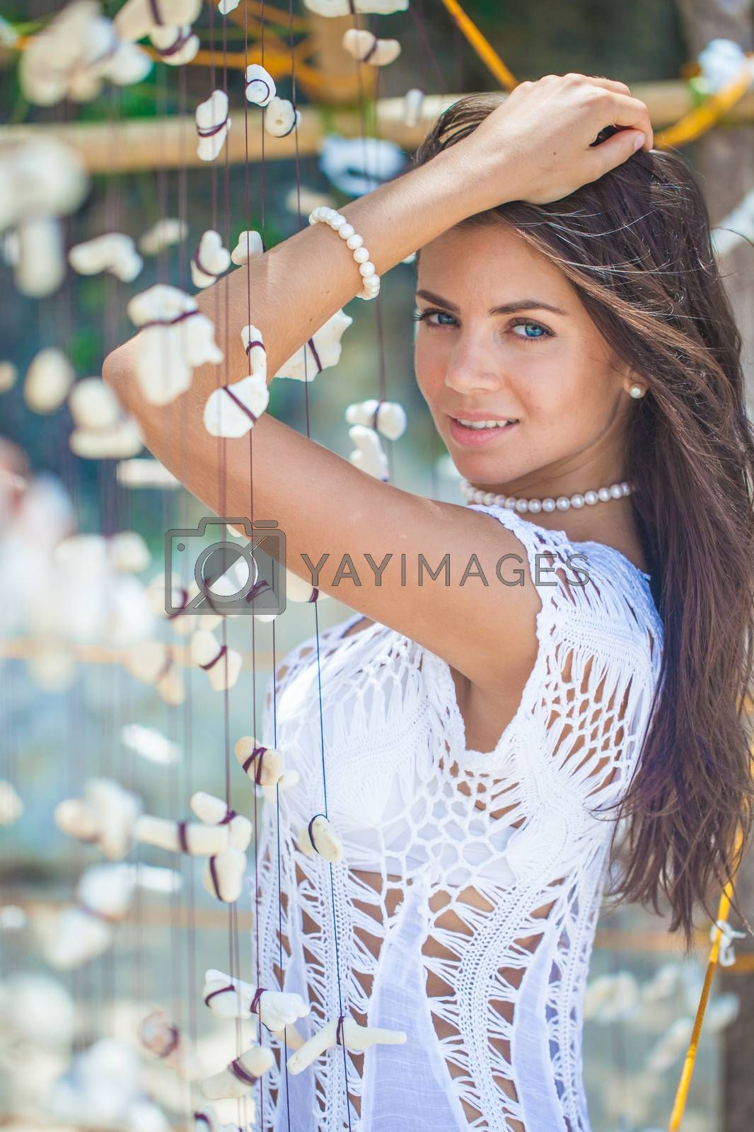 Beautiful woman in white dress on vacation touching a garland of shells and corals