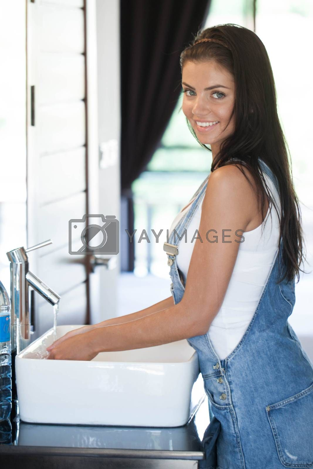 Side view of beautiful young woman in bathroom washing hands
