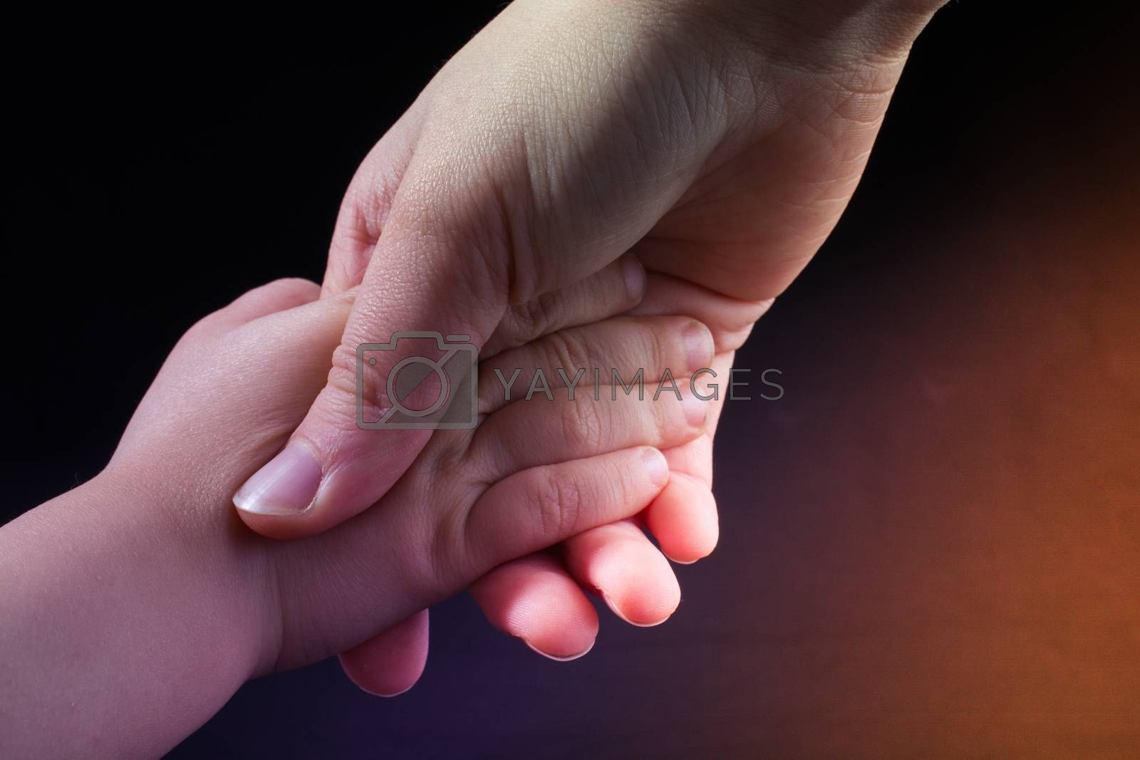 Adult and child hold hands in black background