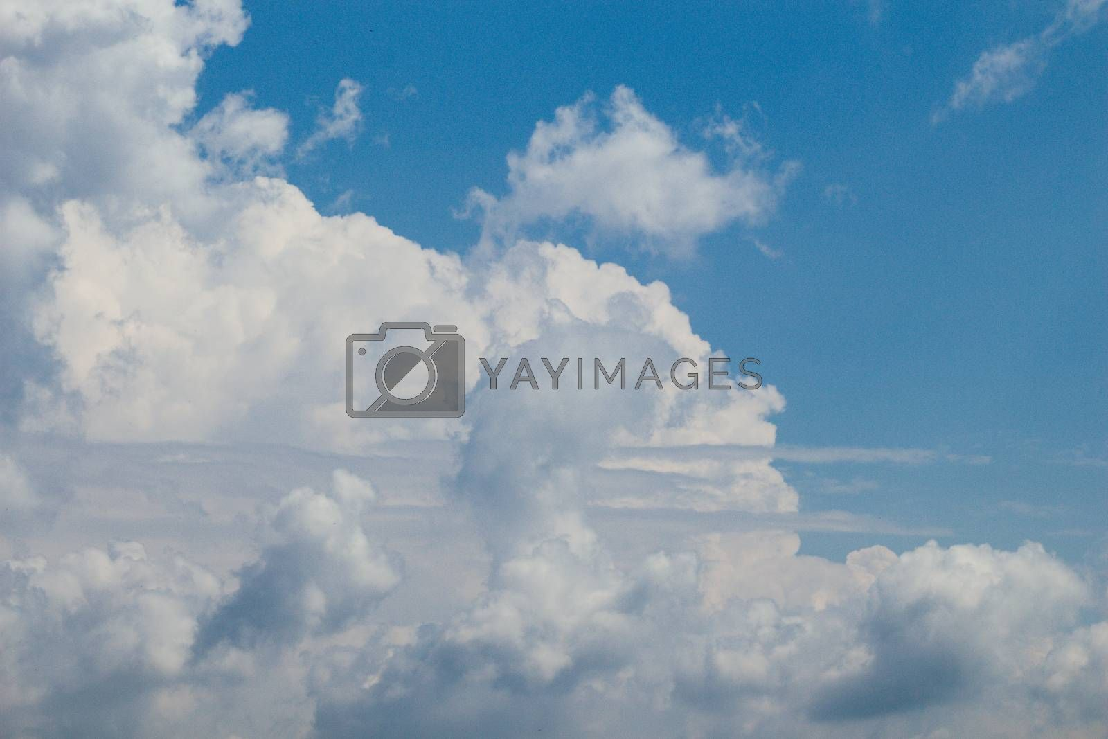 White color clouds cover the blue sky in the daytime