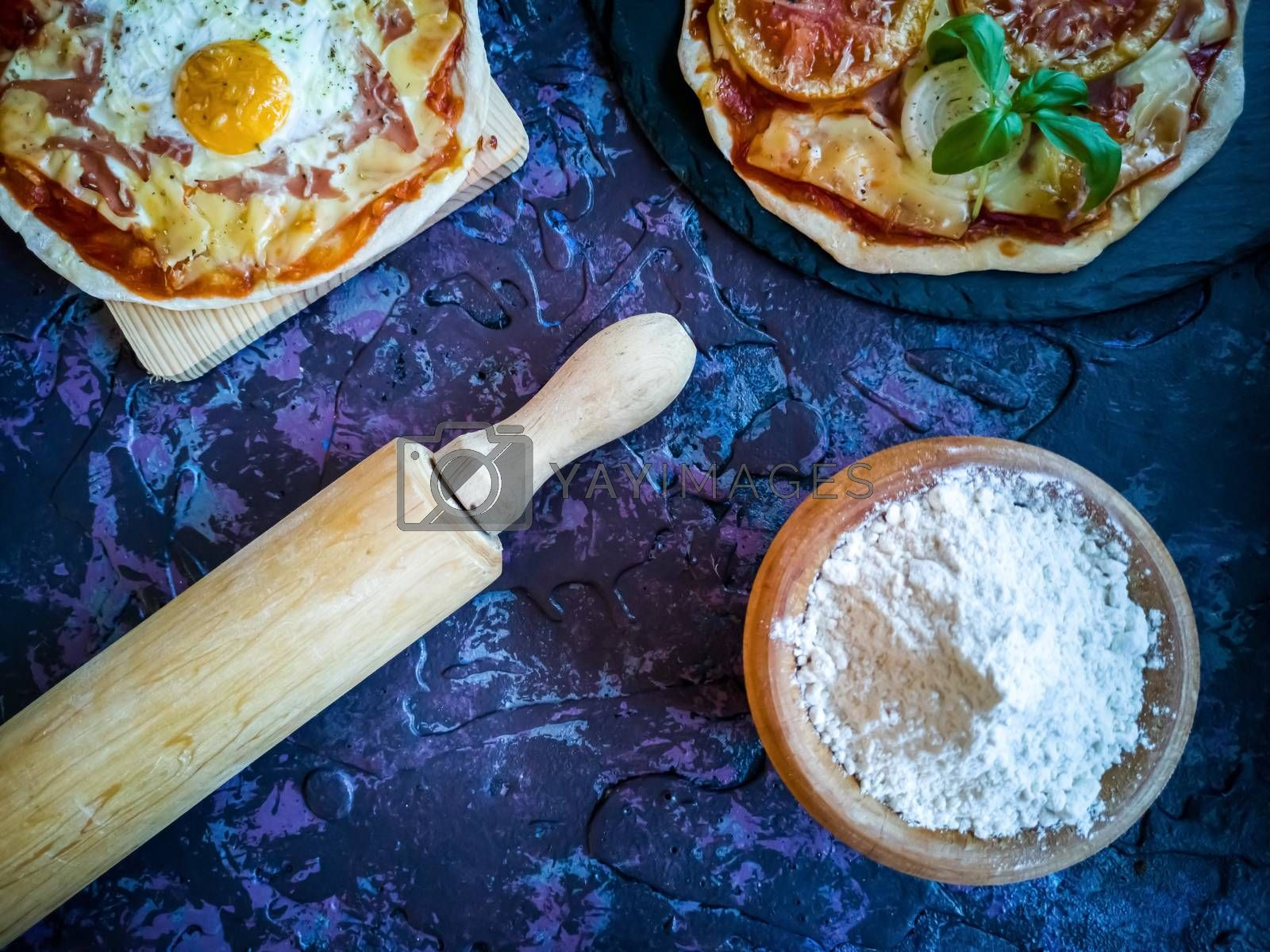 Homemade pizzas and utensils on dark background in lilac tones