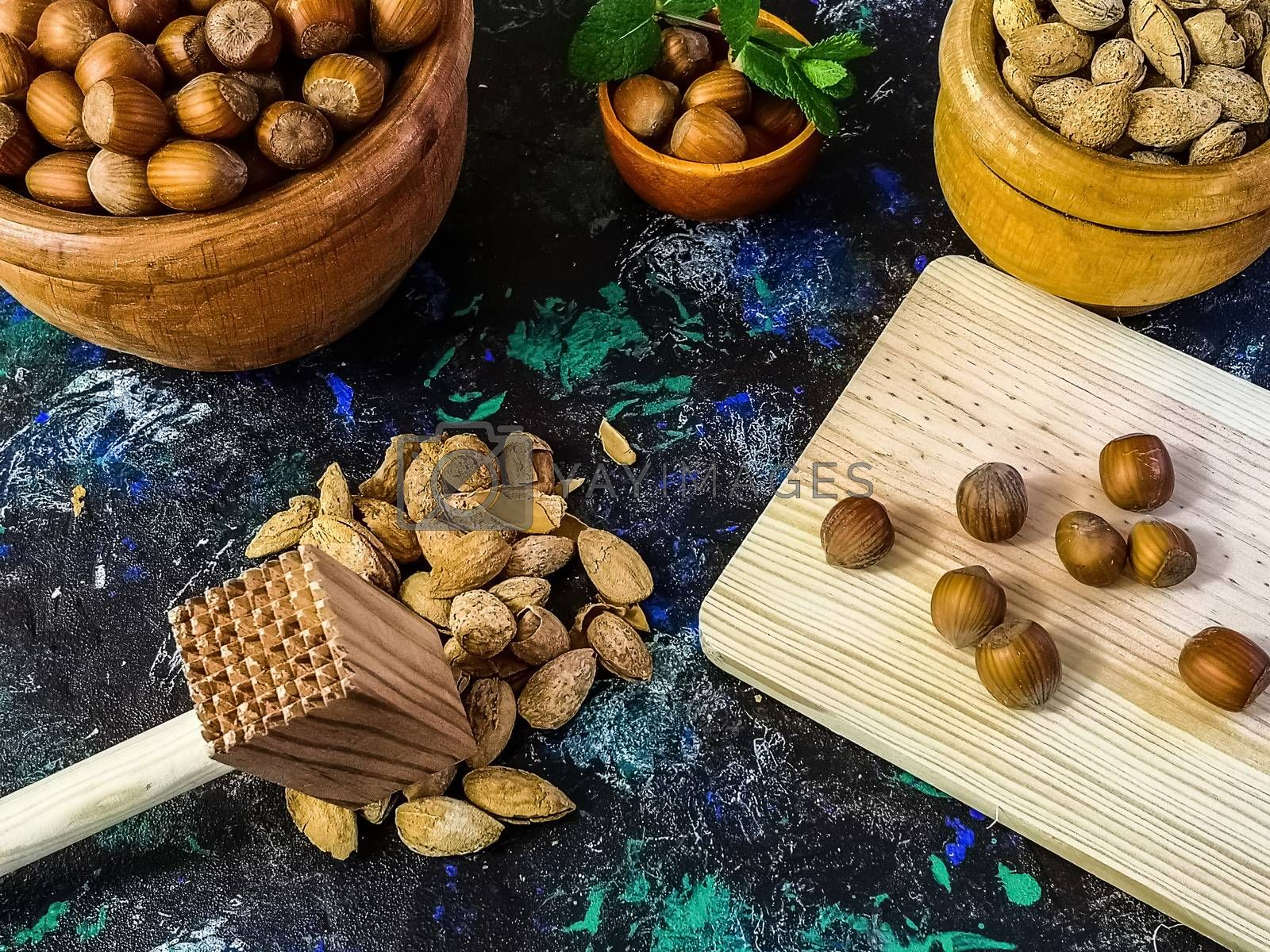 Walnuts and hazelnuts in composition on dark and rough background