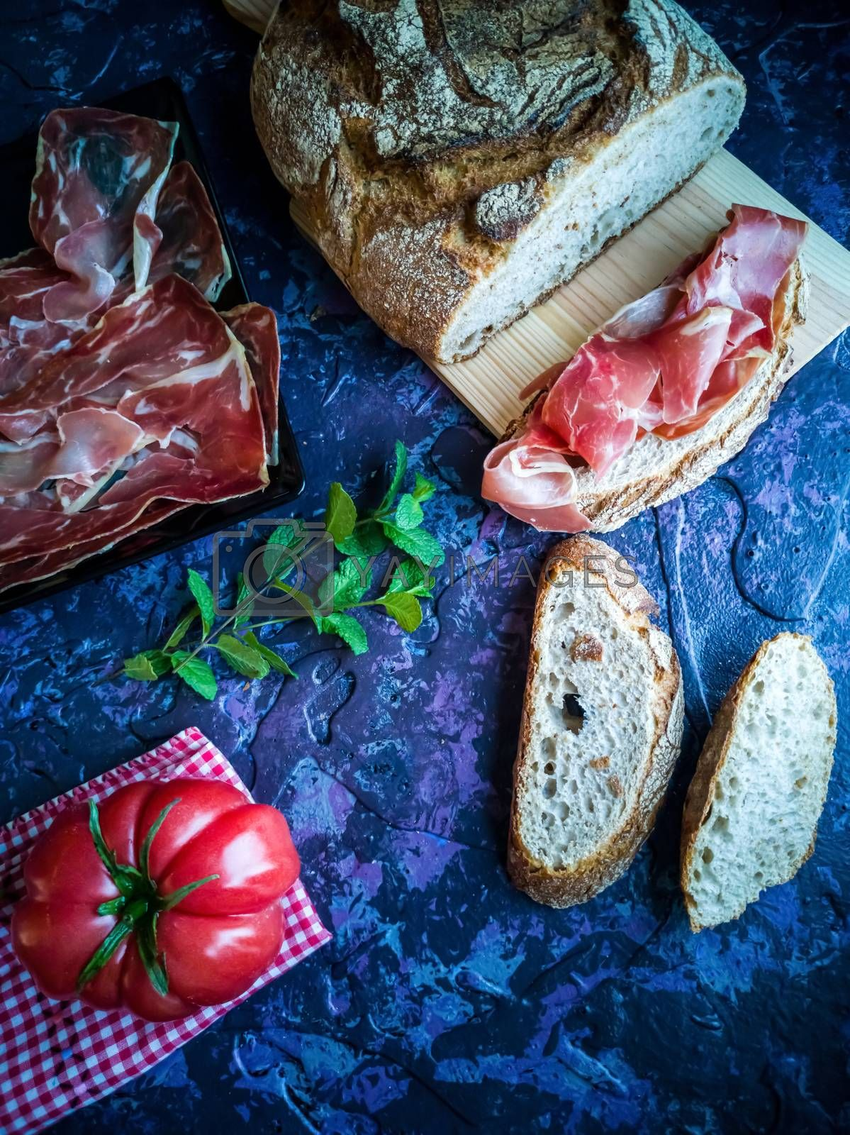 Ham, tomato, bread and herbs in composition on dark background with rough texture