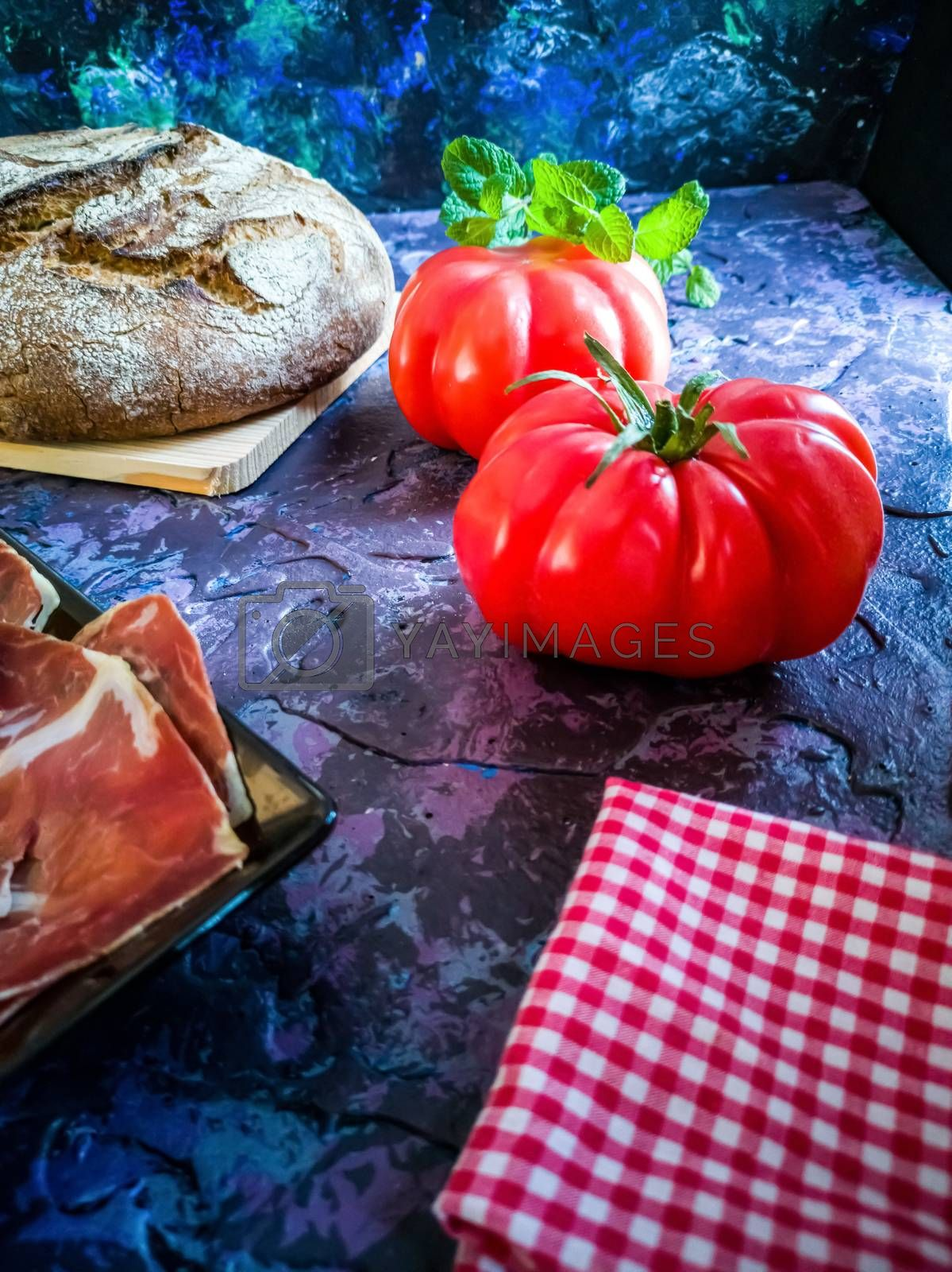 Ham, tomato, bread and herbs in composition on dark background by Barriolo82