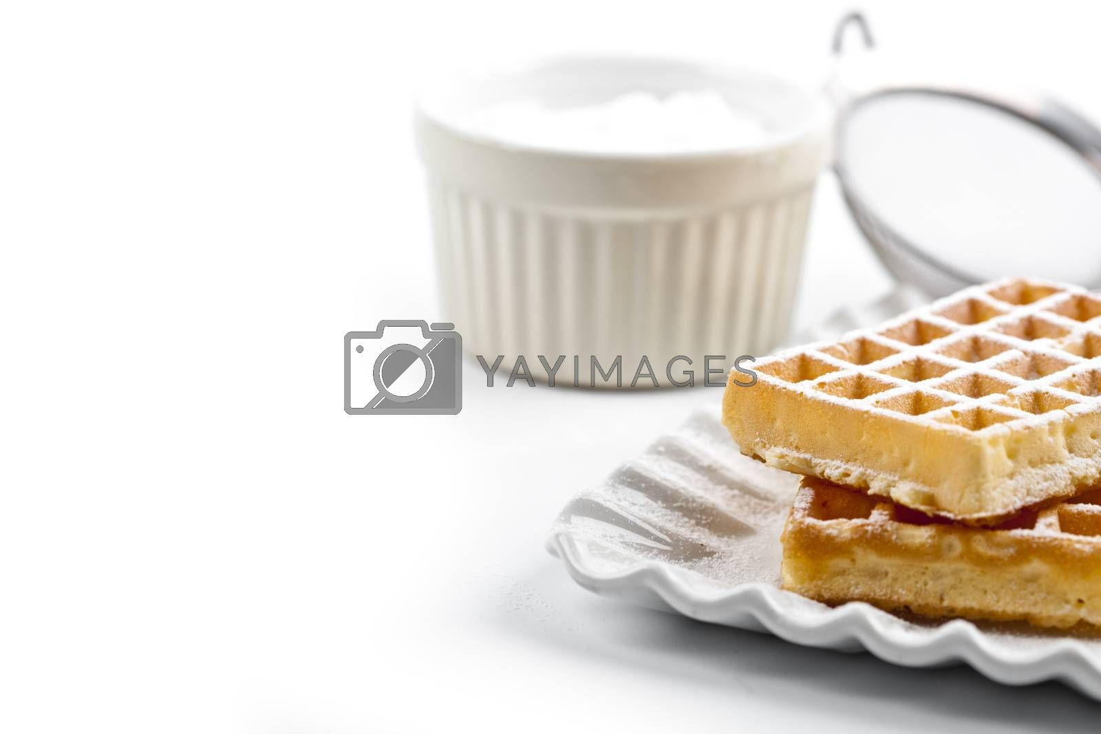 Belgium waffers with sugar powder on ceramic plate and strainer  by marylooo