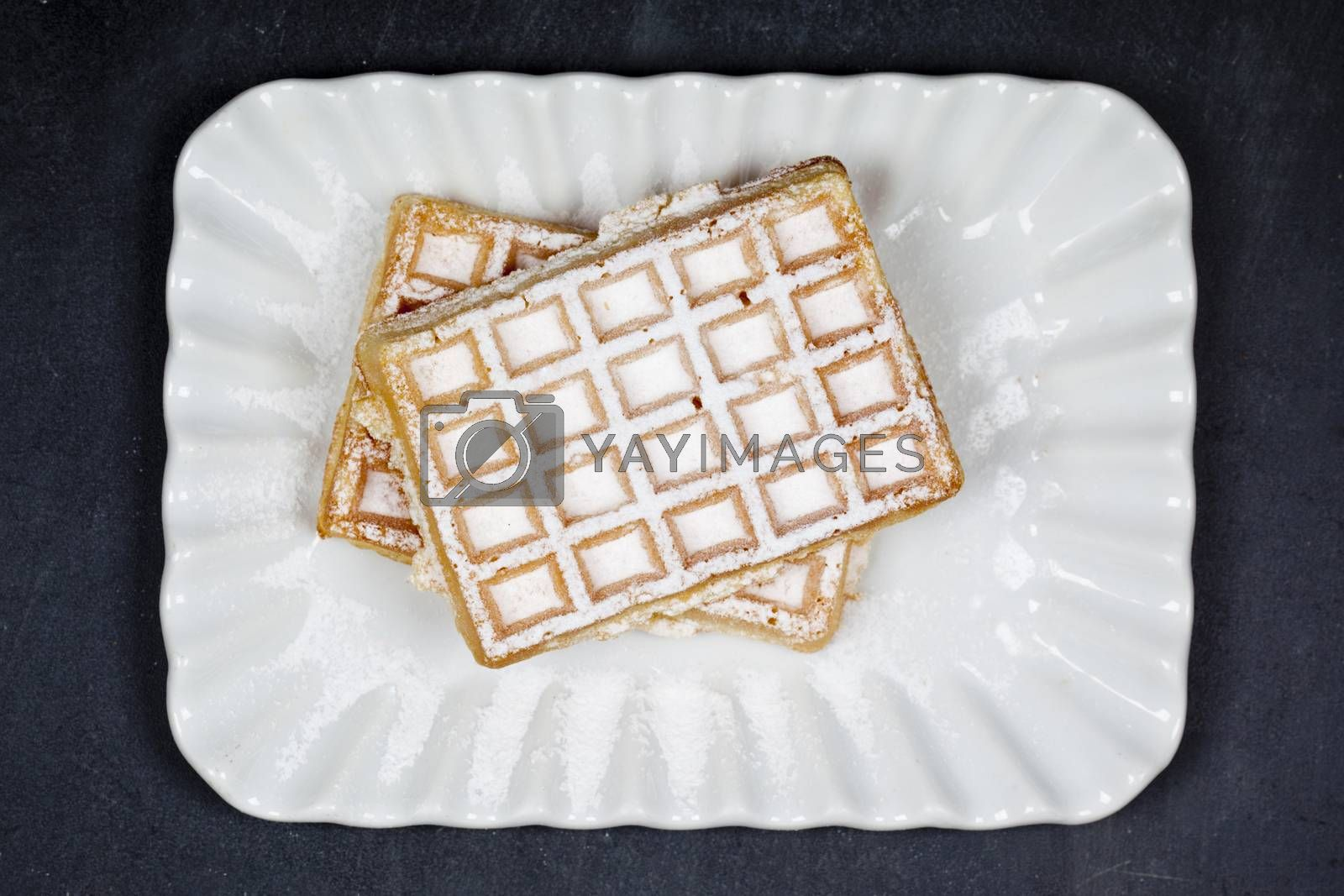 Belgium waffers with sugar powder on ceramic plateon black board background. Fresh baked wafers top view.