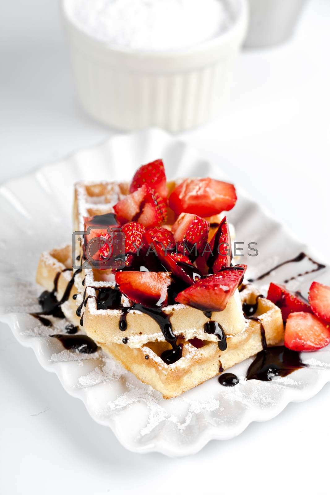 Belgium waffers with sugar powder, strawberries and chocolate on ceramic plate on white table. Fresh baked wafers with copy space.