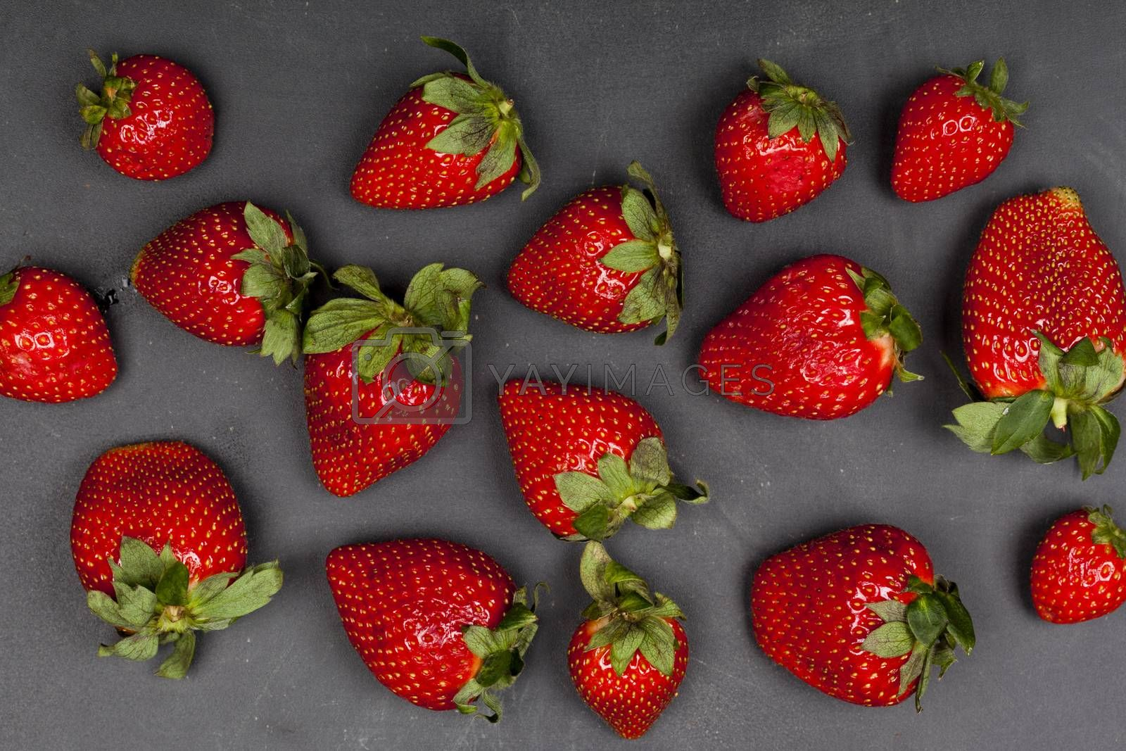 Fresh ripe strawberries on black background, top view.