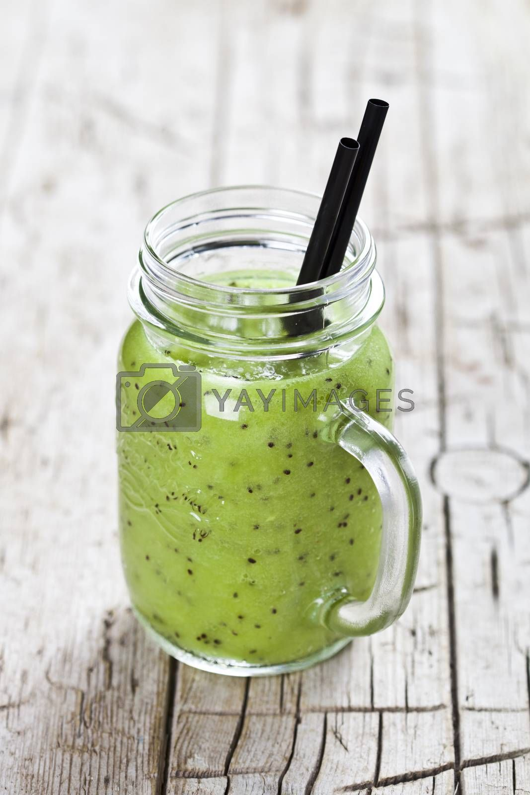 Green smoothie with kiwi, apple, lime and linen seeds. Healthy fresh diet eating, superfood on wooden rustic background.