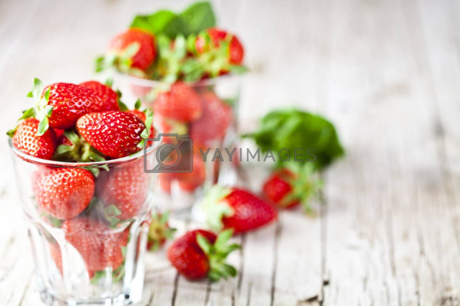 Organic red strawberries in two glasses and mint leaves on rustic wooden background. Healthy sweet food, vitamins and fruity concept. With copy space.