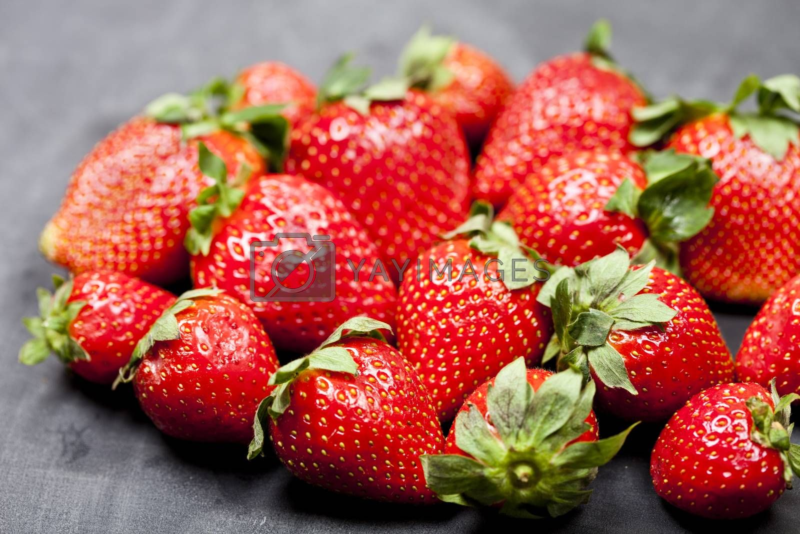 Fresh ripe strawberries closeup on black background.