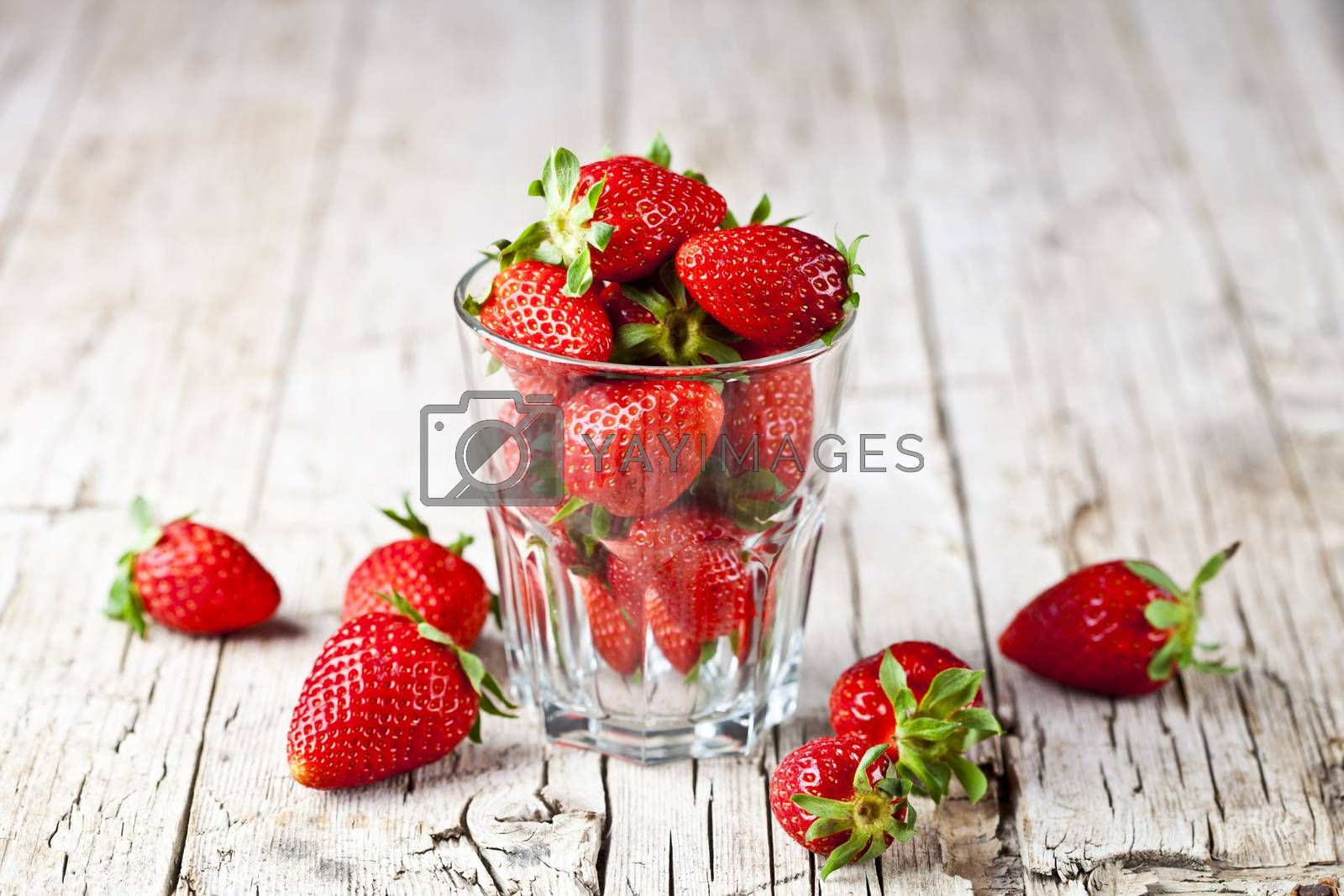 Organic red strawberries in glass on rustic wooden background. Healthy sweet food, vitamins and fruity concept.