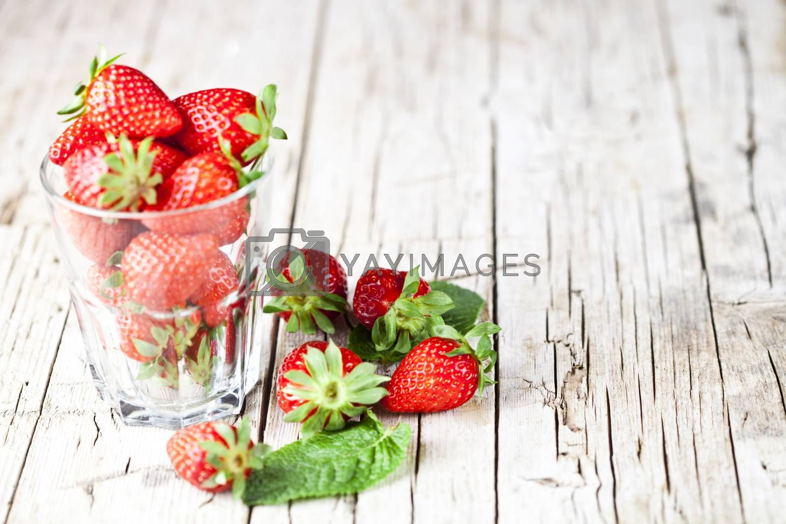 Organic red strawberries in glass and mint leaves on rustic wooden background. Healthy sweet food, vitamins and fruity concept. With copy space.