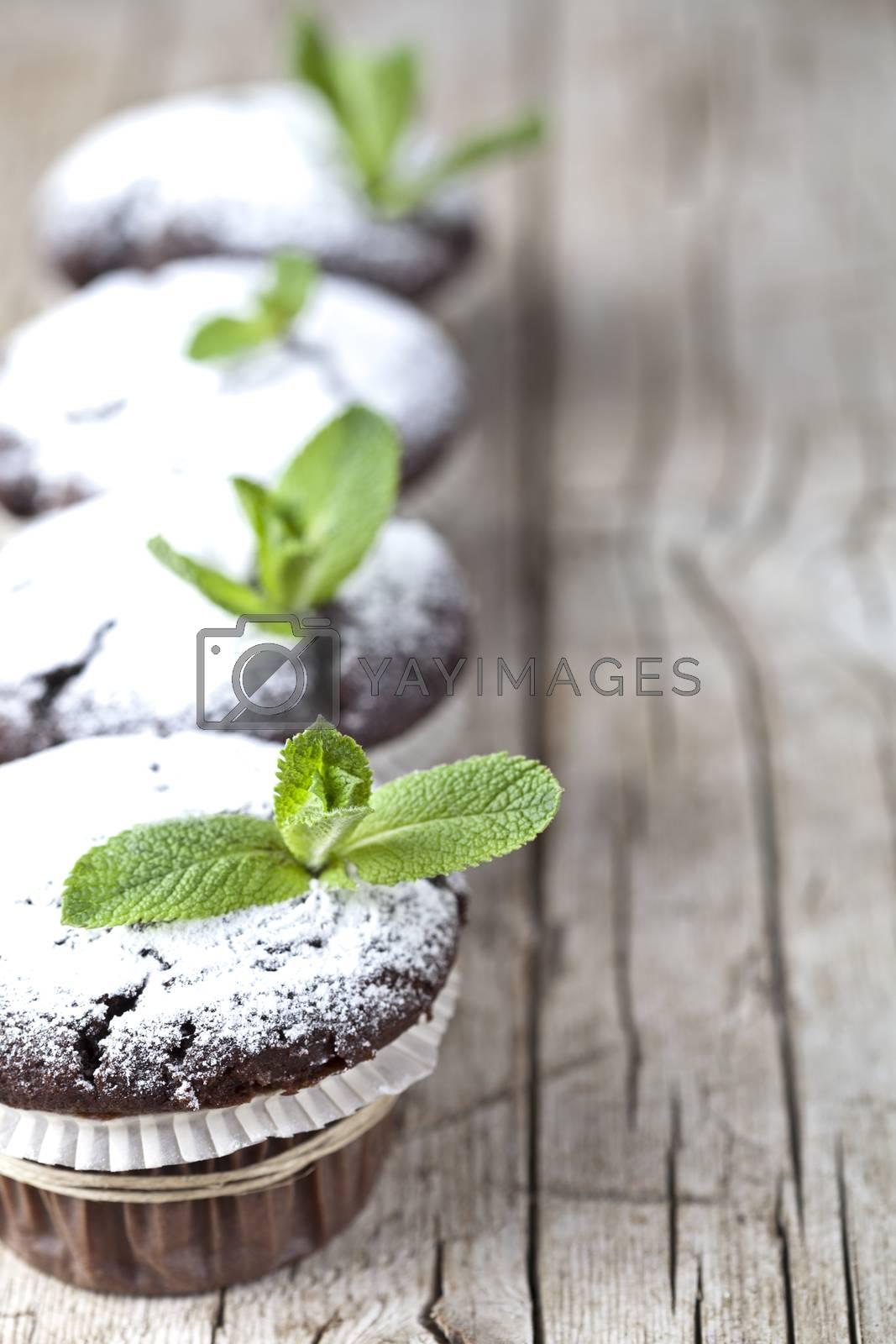 Fresh chocolate dark muffins with sugar powder and mint leaf on  by marylooo