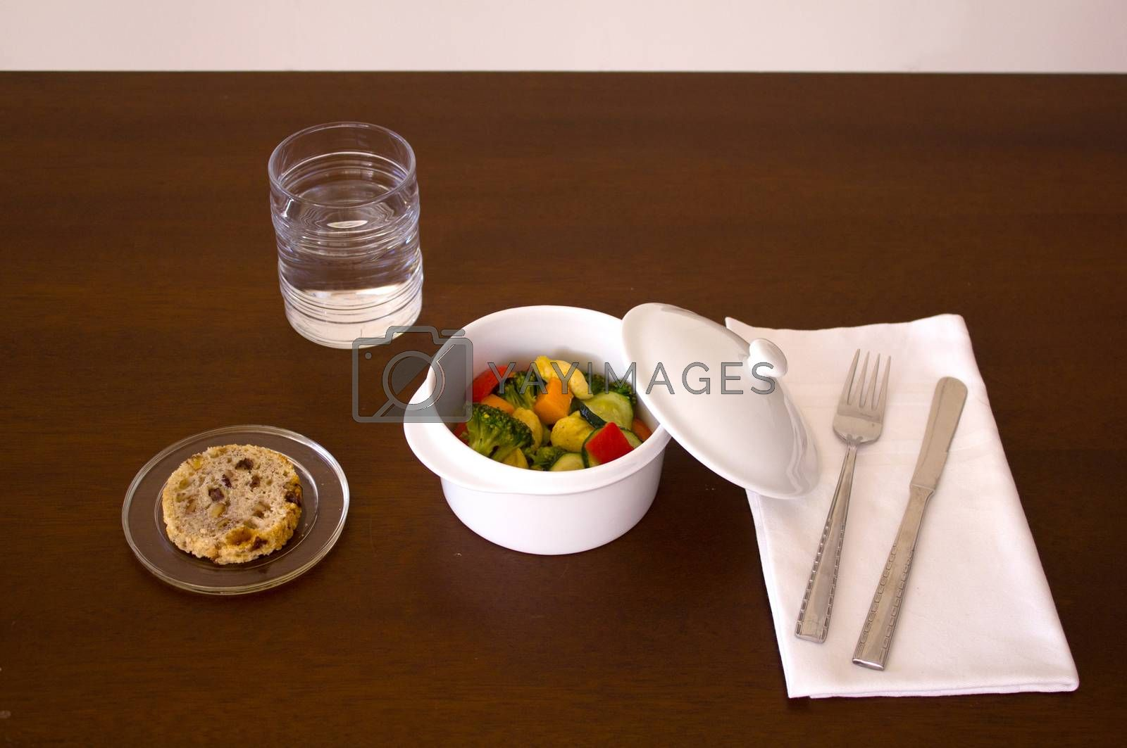 Main course dish, chicken with vegetables, bread, water knife, fork and towel