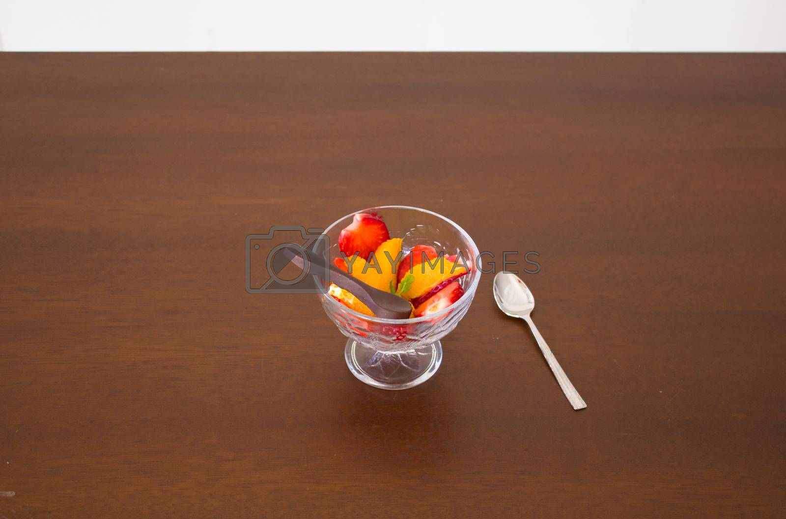 Salad fruit bowl with strawberries, orange and a chocolate spoon for dessert
