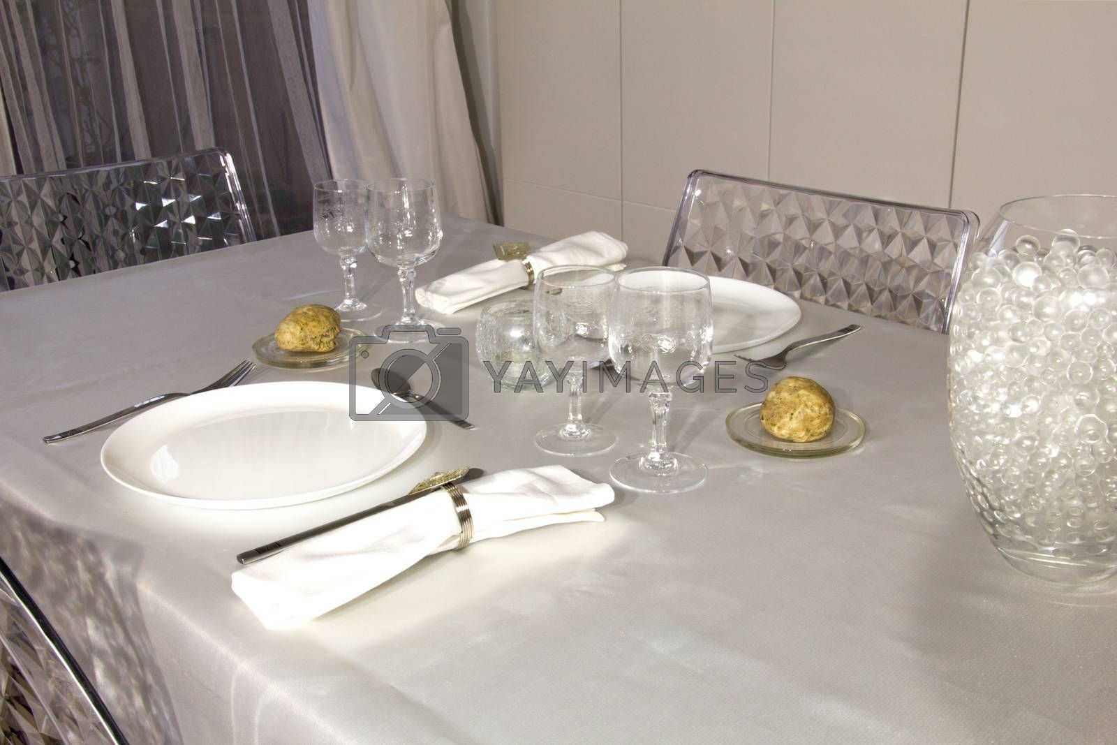 Dishes, cups, cutlery, napkins,candle, decor and bread served on the table with white tablecloth