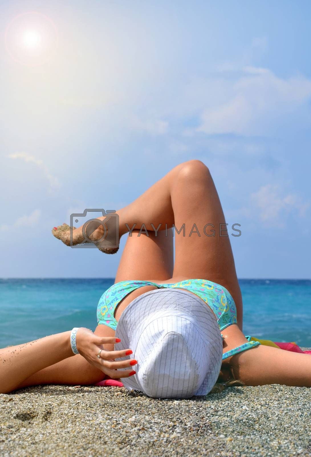 Happy young woman in bikini and hat sunbathing on tropical beach, luxury vacation concept, copy space.