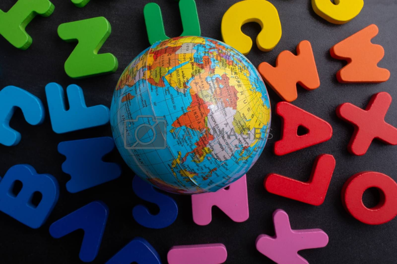 Earth globe model on colorful letters on a black background