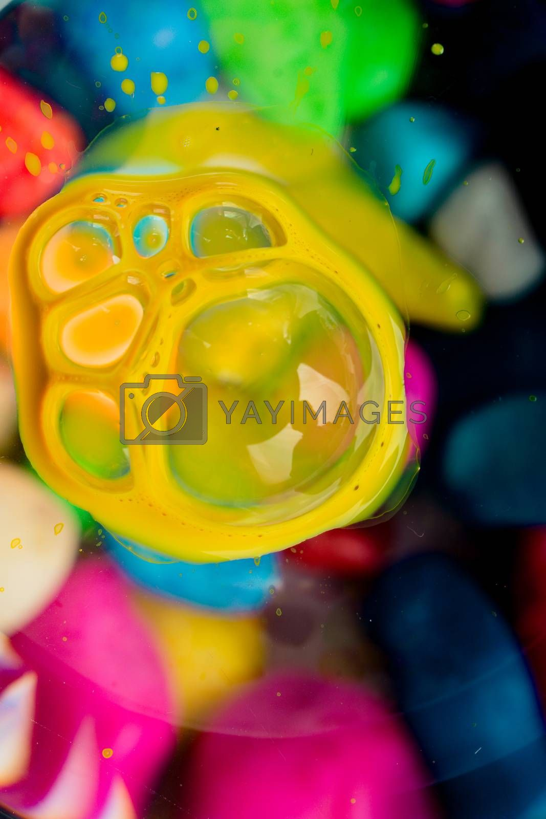 Colorful paint bubbles on a glass backround