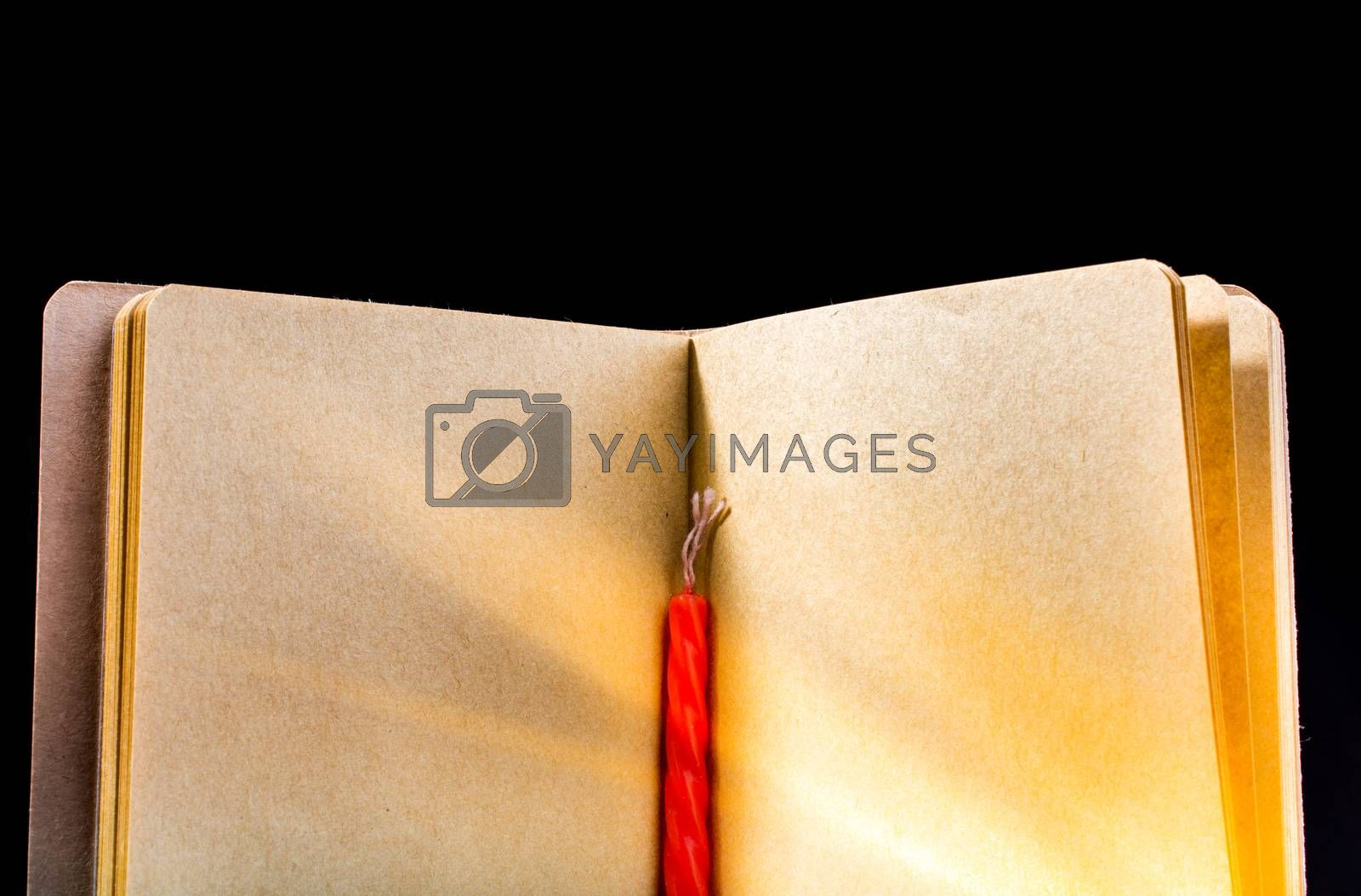 Candle and open brown color notebook on a black background