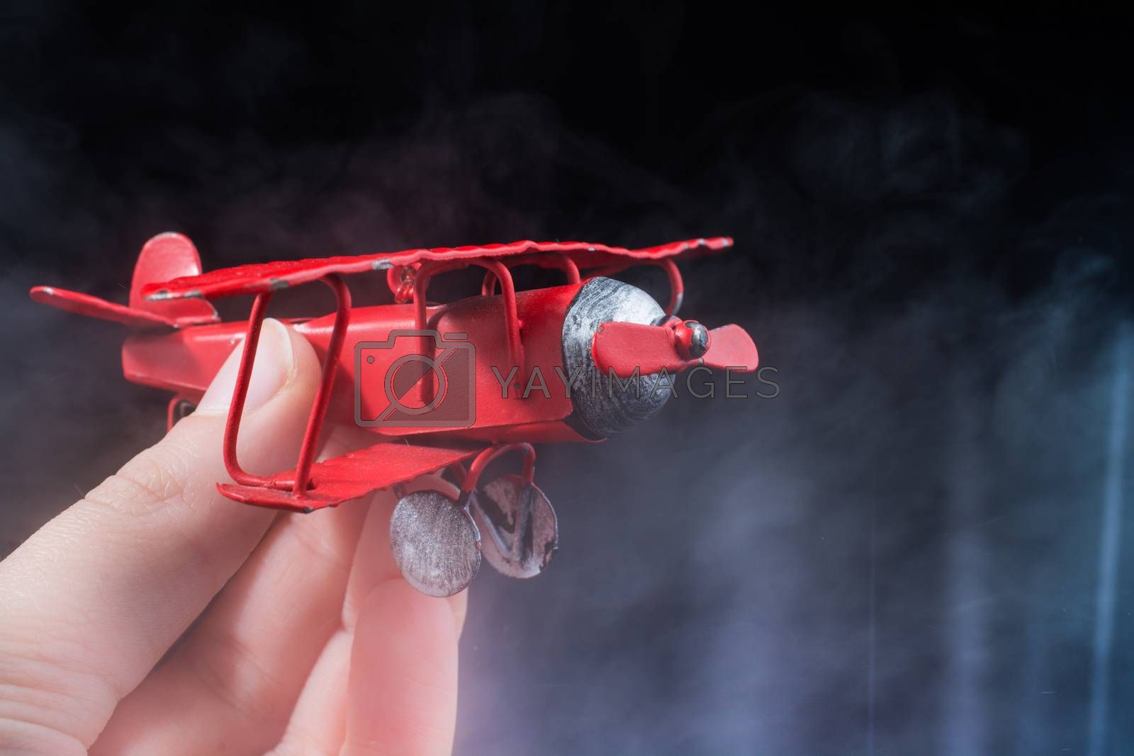 Hand holding a red toy plane on a black background