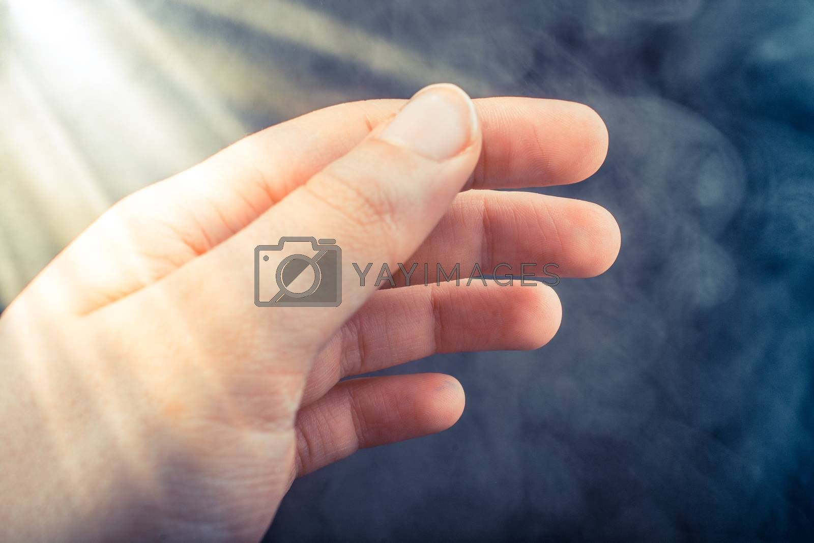Hand making a gesture on black smoky background by berkay