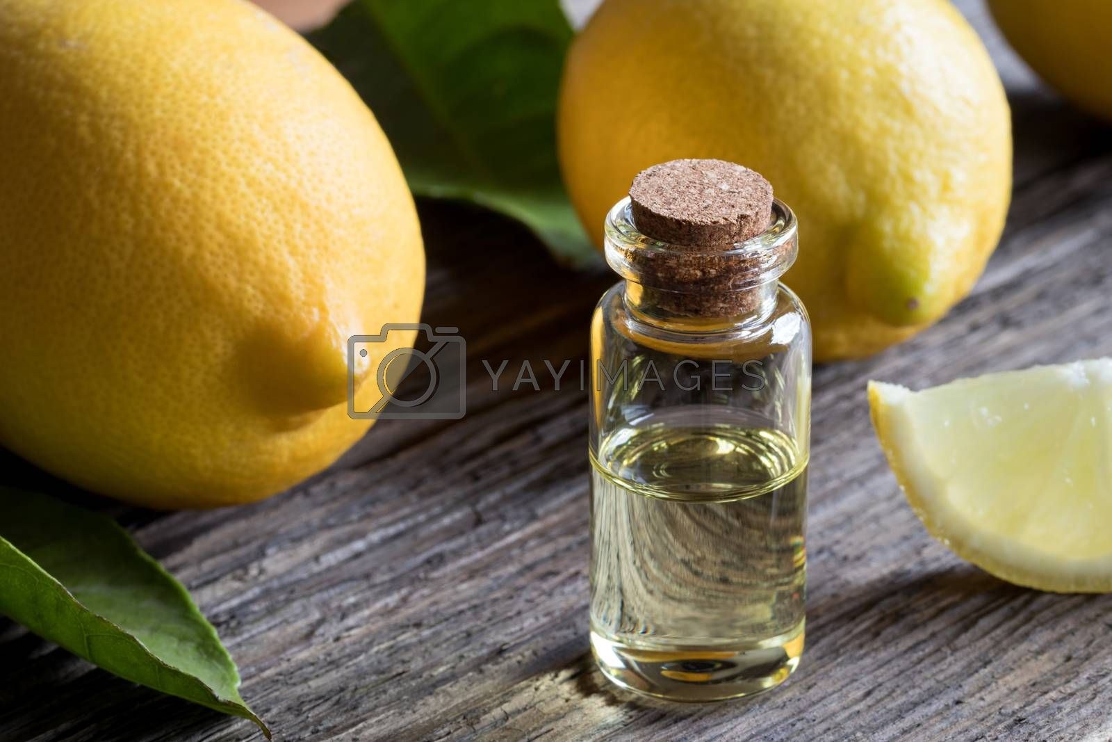 A bottle of lemon essential oil on old wood, with lemons in the background