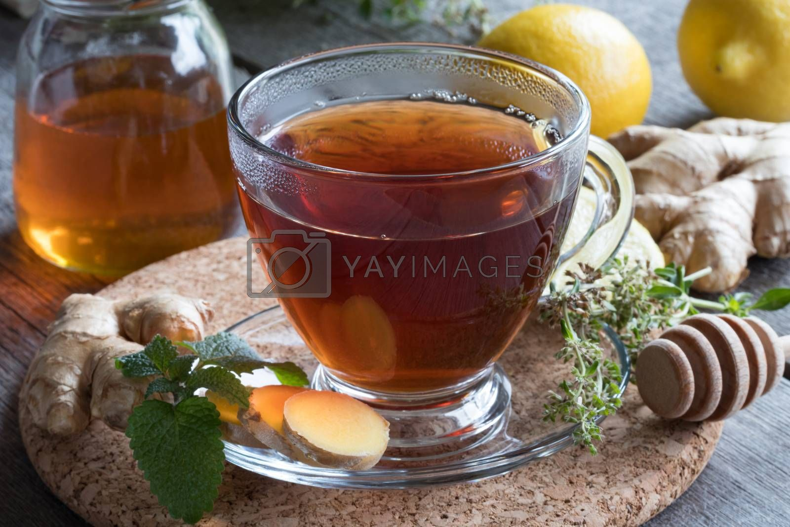 A cup of tea with ginger, melissa and creeping thyme, with lemons and a jar of honey in the background