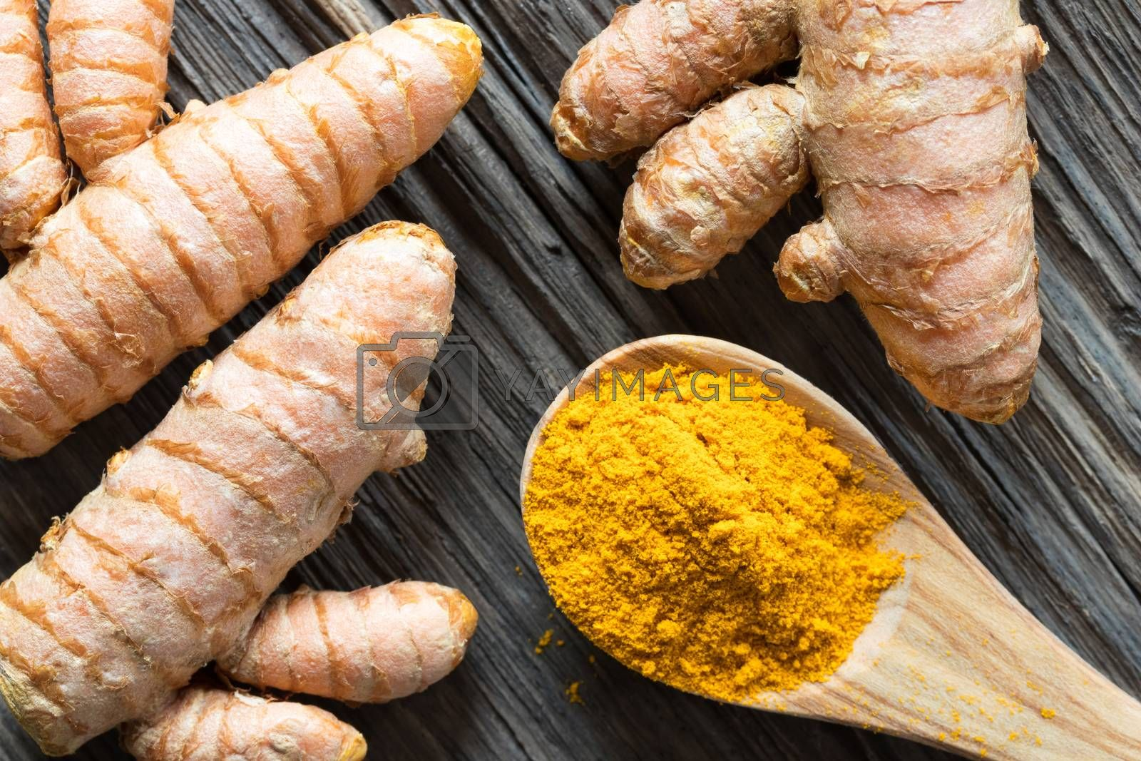 Turmeric powder and fresh turmeric root on a wooden background