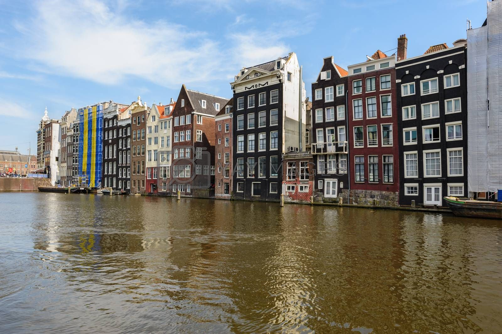 Spirngtime view of the Dancing Canal Houses of Damrak, iconic canal houses in the capital city of Amsterdam, Netherlands