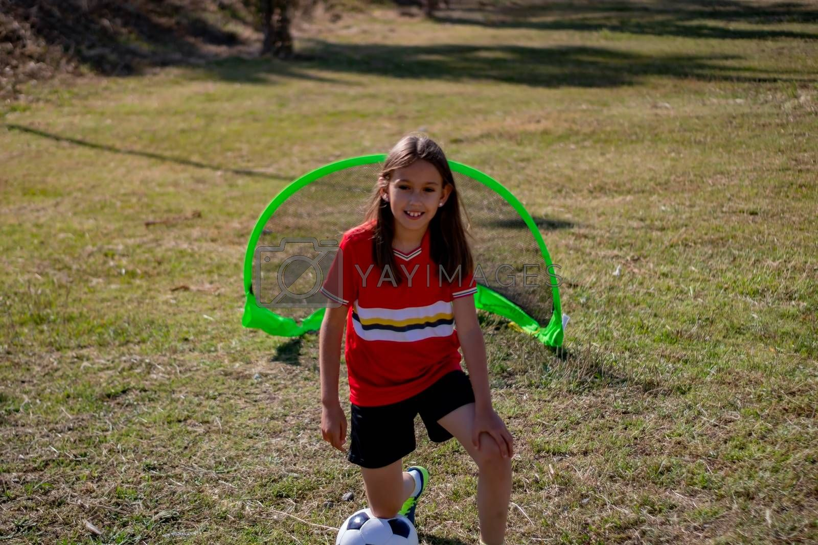 Little girl playing soccer on grassy esplanade