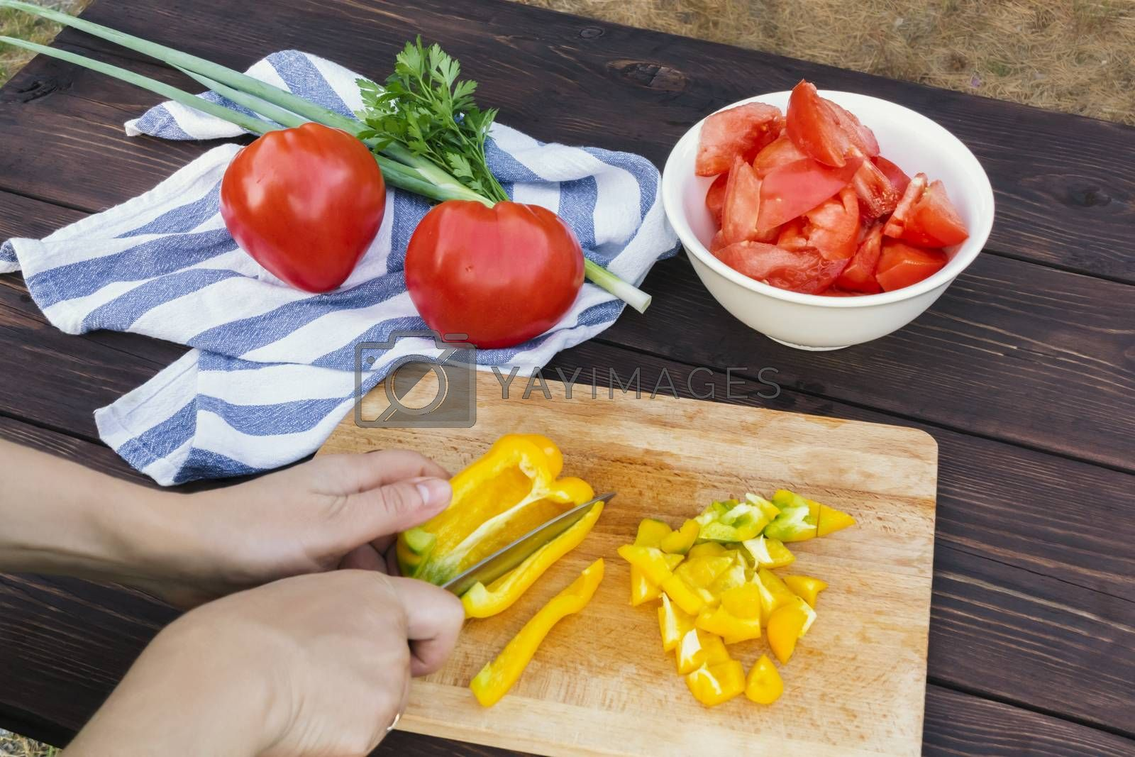 Close Up of woman hands cooking vegetable salad in kitchen on the wooden table. Healthy meal, and vegetarian food concept by galsand