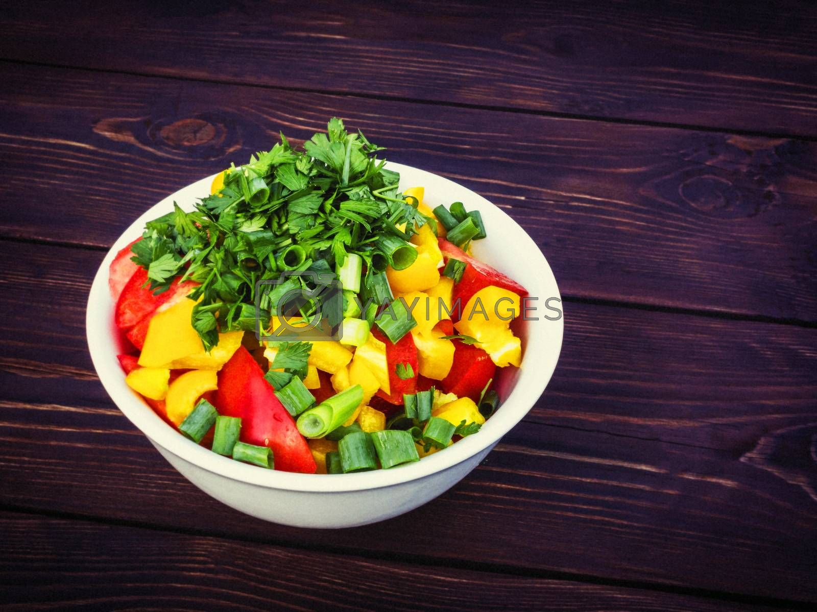 Fresh vegetable salad with herbs in a white bowl on a dark wooden table by galsand