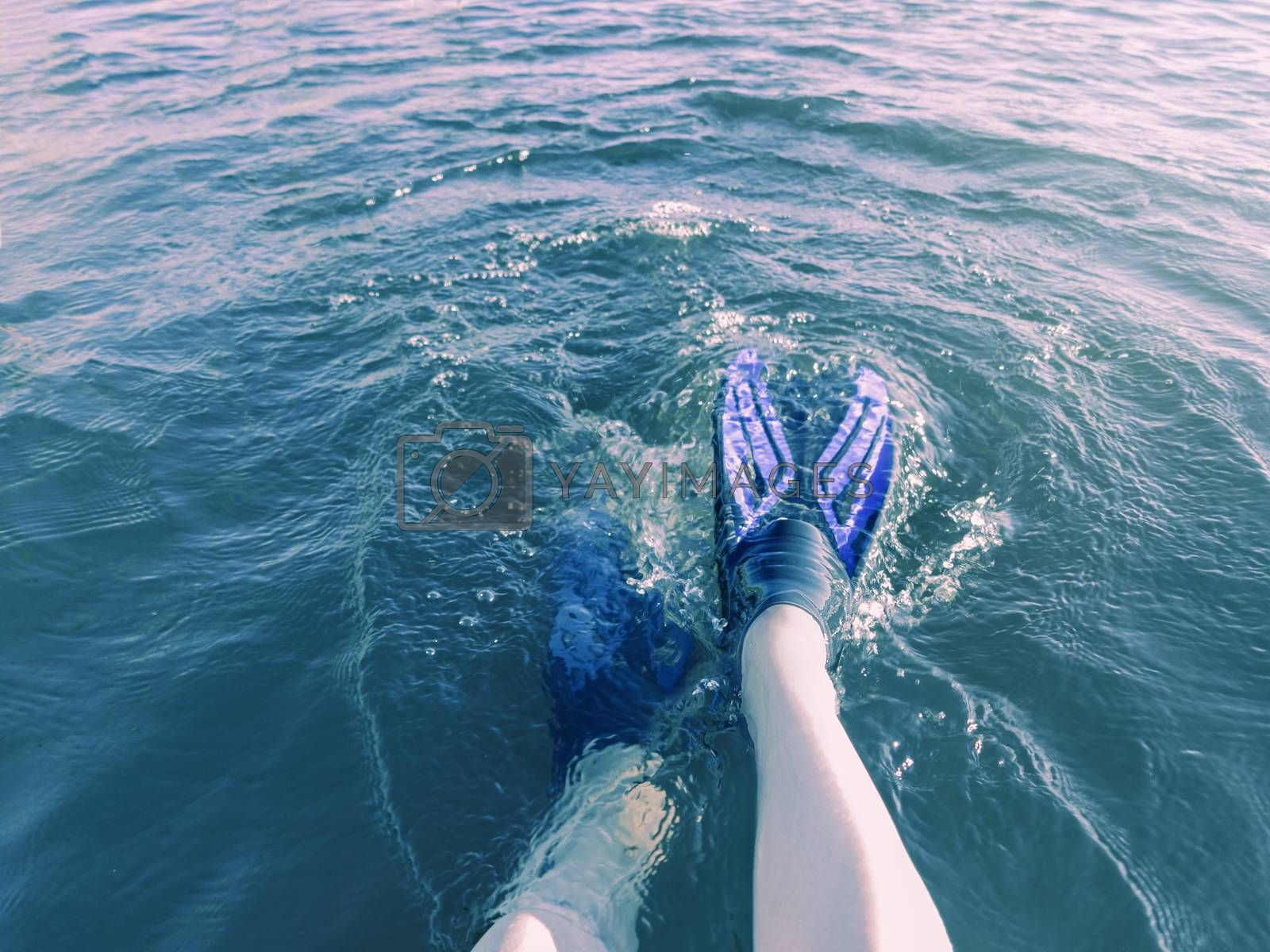 Legs in flippers fall into the blue water in the sun on a hot summer day by galsand