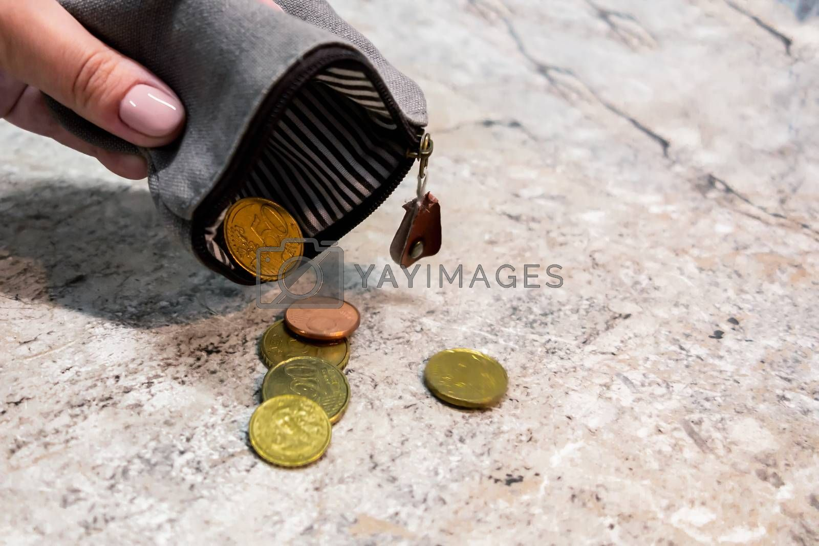 Several coins fall from an empty purse in a woman's hand by galsand
