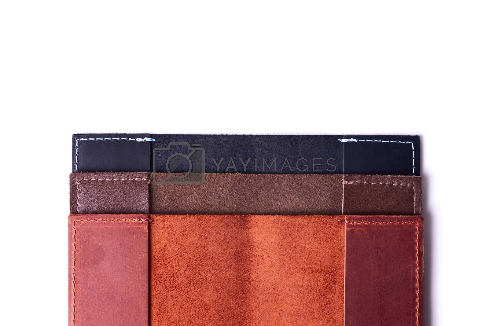Three handmade leather passport covers stack isolated on white background. Closeup view. Covers are dark blue, red, brown and opened. by alexsdriver