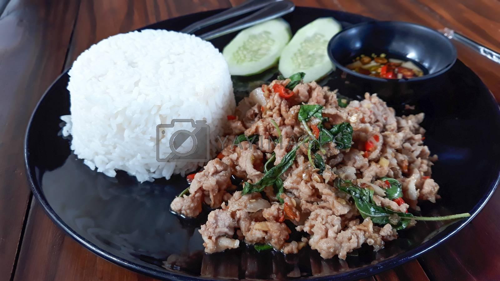 Rice with stir-fried pork and basil ,Thai food. by Nunnicha Supagrit