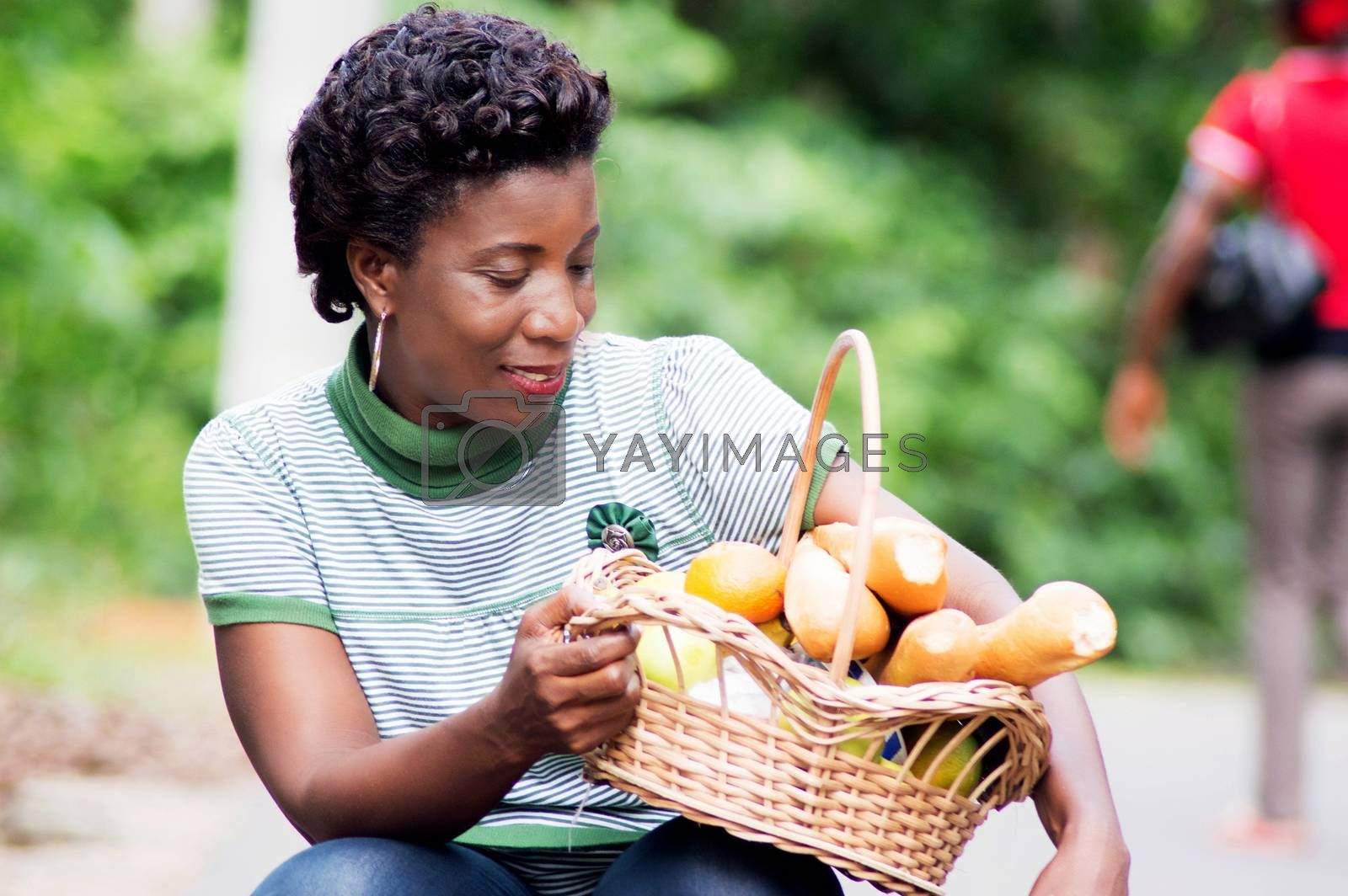 crouching young woman holds on her thigh a food basket by vystekimages