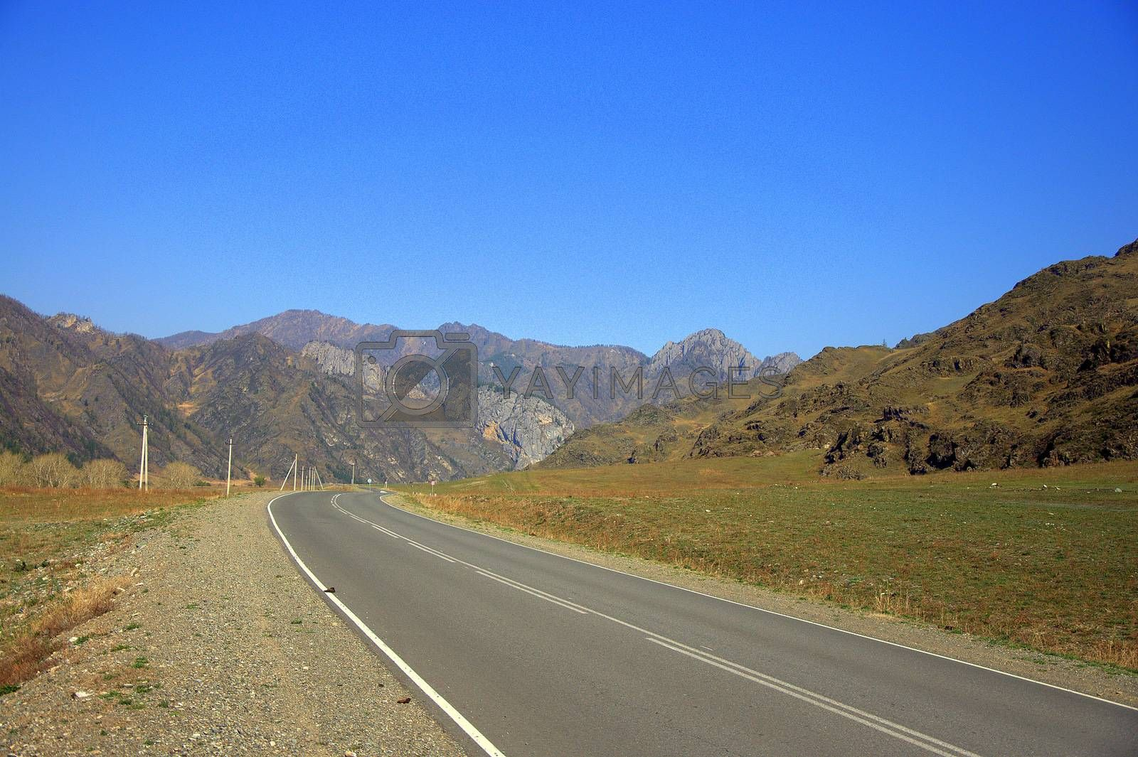 A good asphalt road winding at the foot of high mountain ranges. by Alex Yellow
