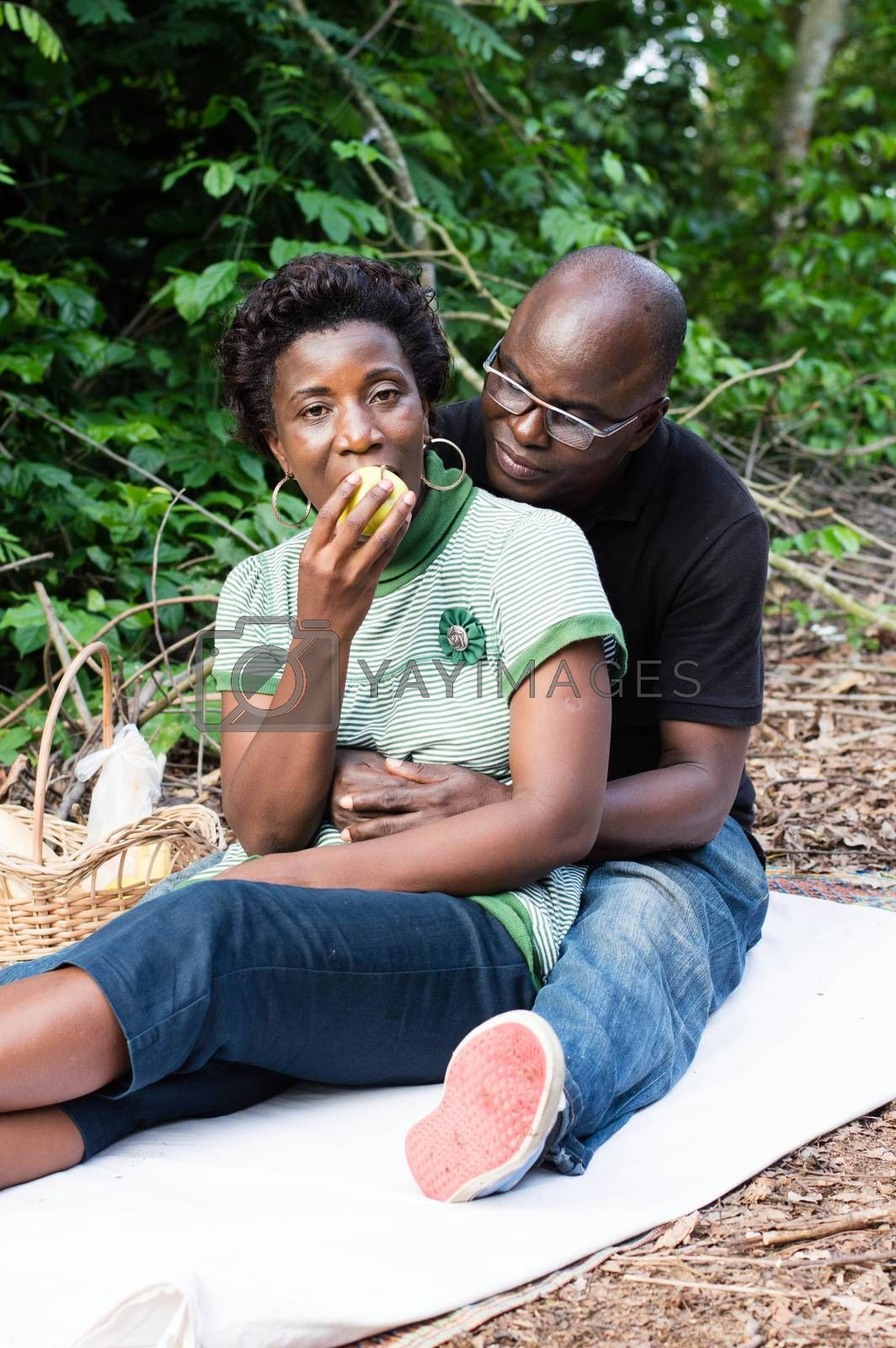 love couple sitting on a mat in the bush. by vystekimages