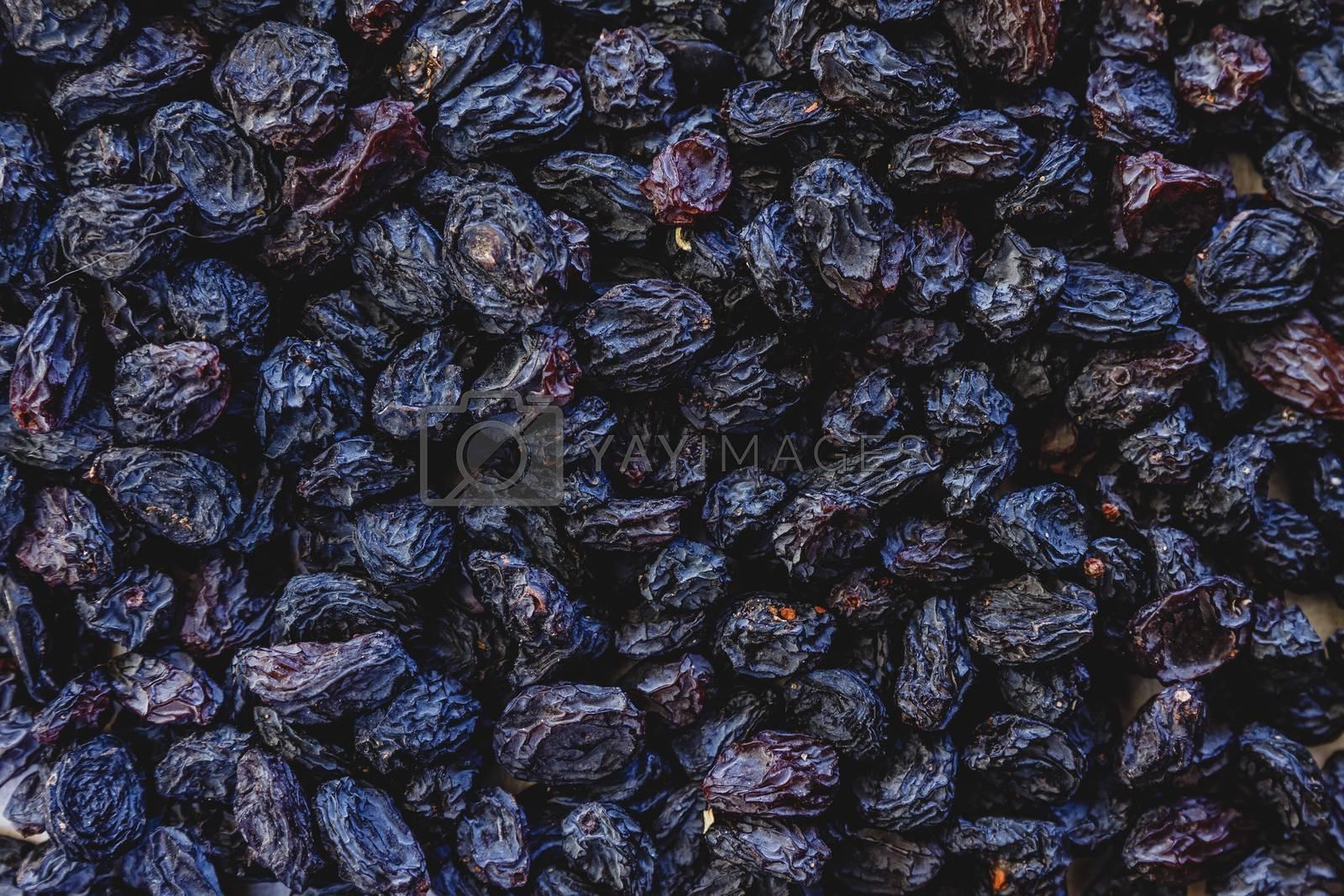 Background from dark blue raisins. Close-up. by Tanacha