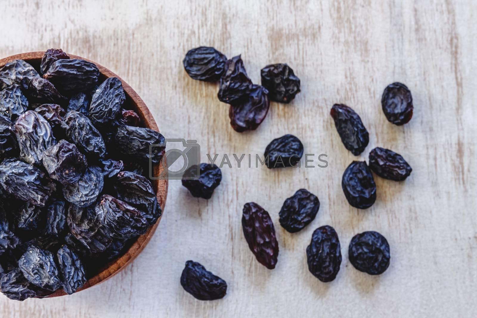 Dark blue raisins in a wooden bowl on a bright white background. by Tanacha