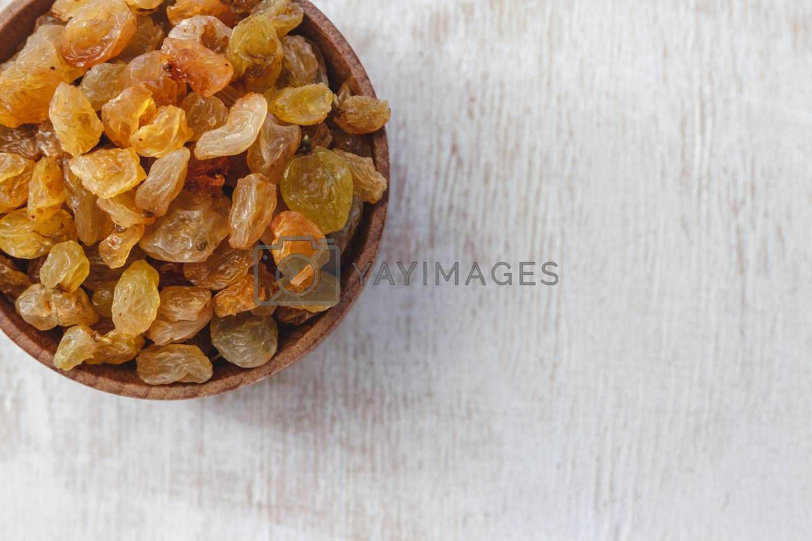Light yellow raisins in a wooden bowl on a light white backgroun by Tanacha