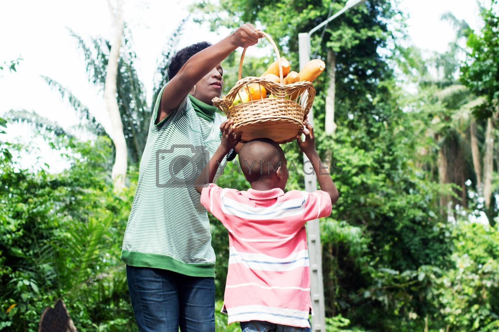 Mom puts the food basket on the head of his son. by vystekimages
