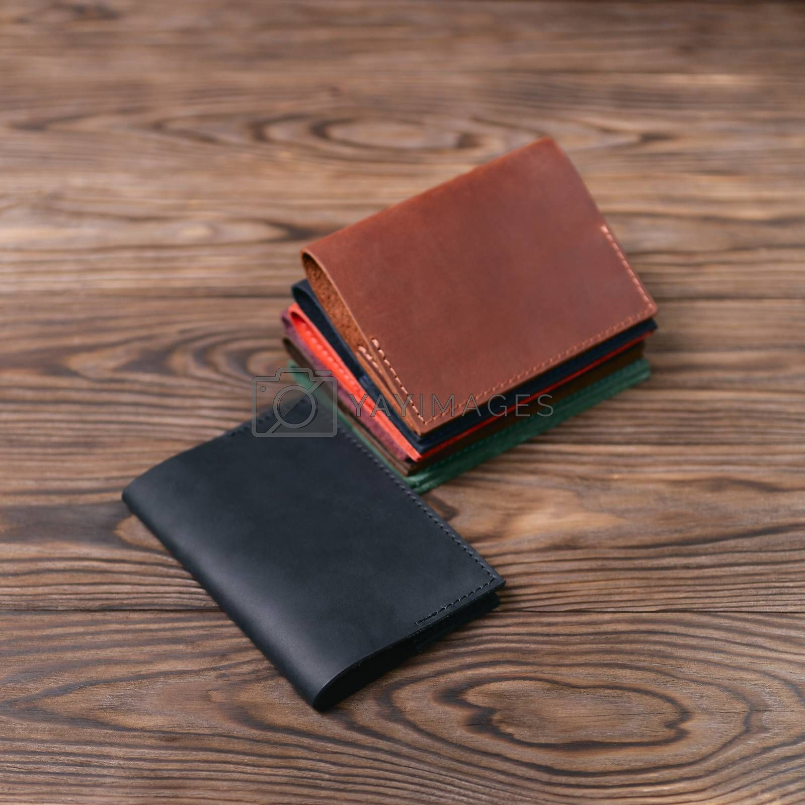 Six handmade leather passport covers on wooden textured background. Stock photo of luxury accessories. by alexsdriver