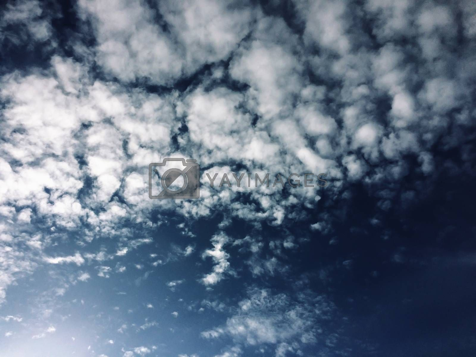 Gloomy autumn blue sky with white clouds natural background by Eskimos