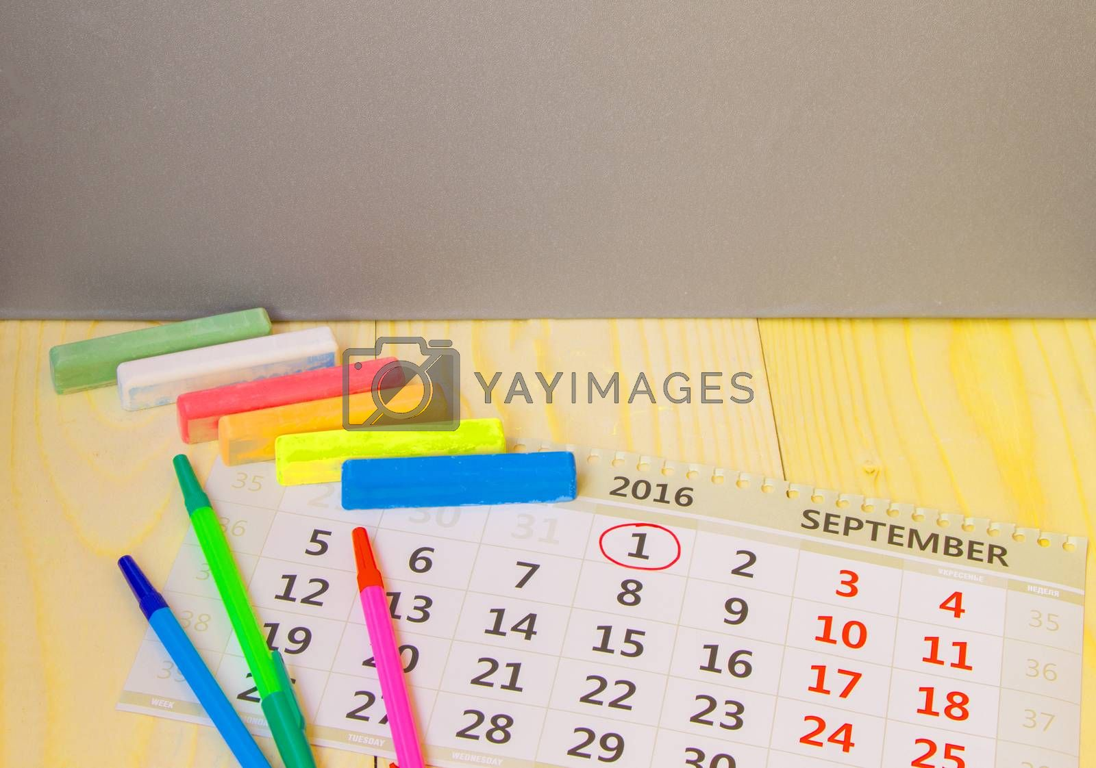 Back to school, calendar, colored chalk on wooden background.